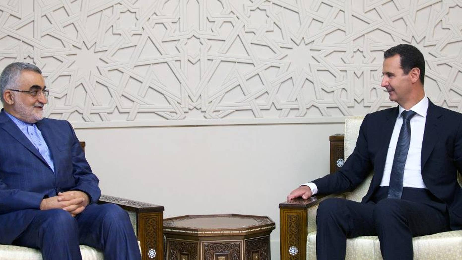"""In this photo released by the Syrian official news agency SANA, Syrian President Bashar Assad, right, meets with Alaeddin Boroujerdi, Chairman of the Committee for Foreign Policy and National Security at the Iranian Shura Council, in Damascus, Syria, Thursday, Aug 4, 2016. Boroujerdi said operation by the Syrian government and allied forces in Aleppo aims to """"liberate"""" tens of thousands of residents from the grip of what he called terrorist groups. (SANA via AP)"""