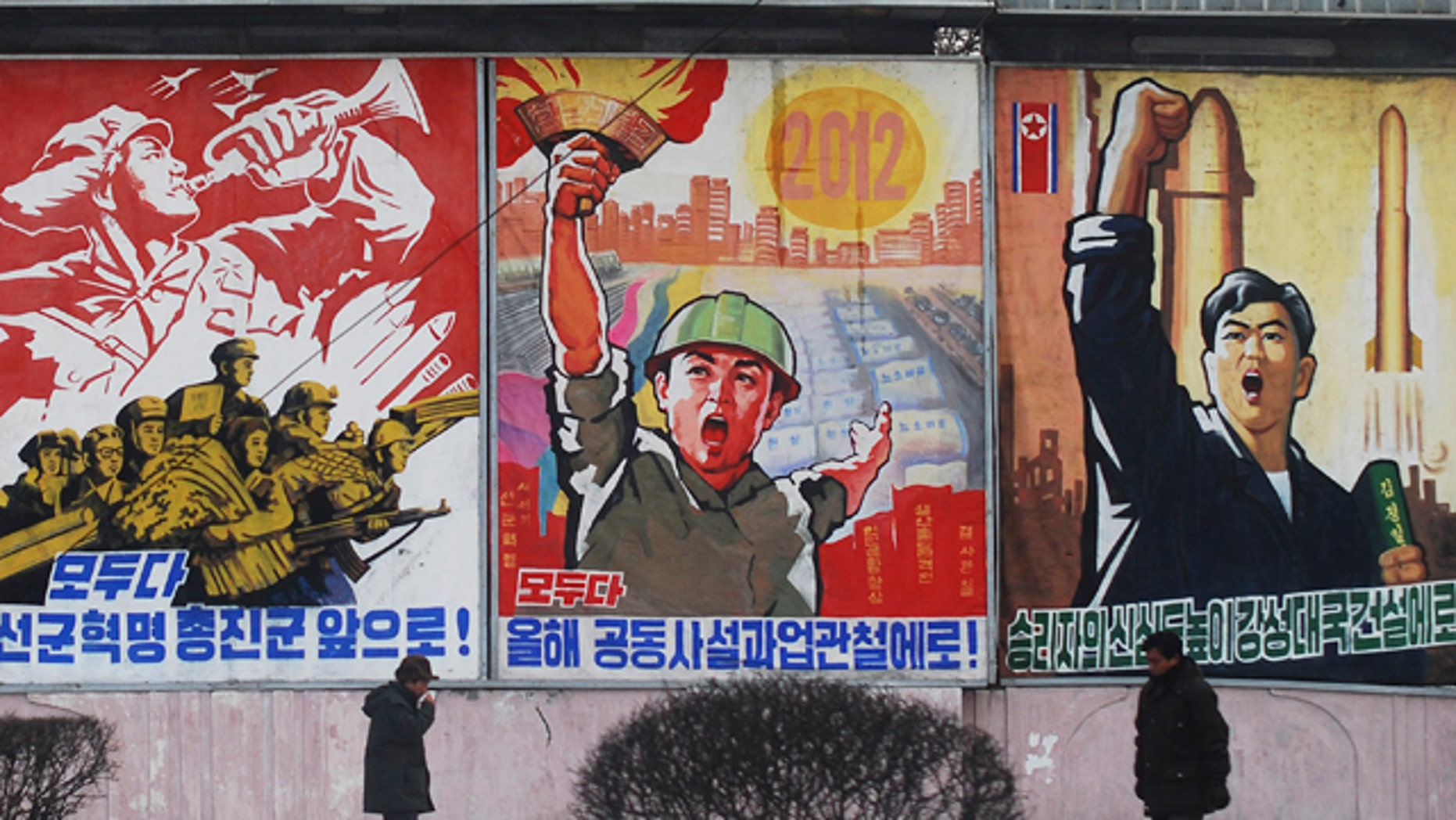 """In this Feb. 11, 2012 photo, residents walk past posters with popular slogans illustrating North Korea's main policies, on a street in Pyongyang, North Korea. From left to right, they read """"Let's march toward a military first revolution,"""" """"Let's accomplish the tasks laid out in this year's joint new year's editorial,' and """"Devote the victors' hearts to the building of a strong nation."""""""