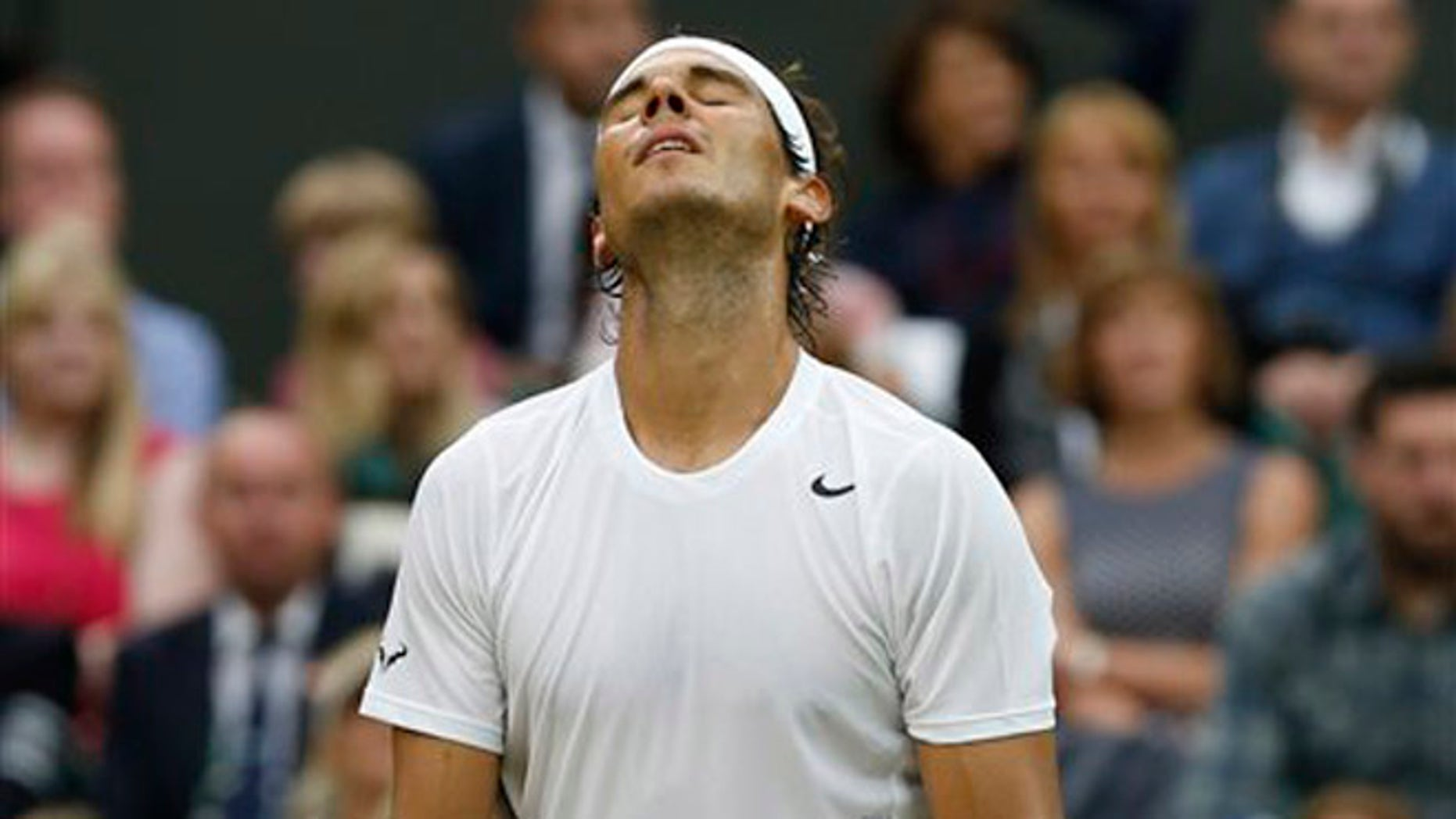 Rafael Nadal of Spain reacts in frustration after missing a point as he plays against Mikhail Kukushkin of Kazakhstan during their men's singles match on Centre Court at the All England Lawn Tennis Championships in Wimbledon, London, Saturday, June 28, 2014. (AP Photo/Ben Curtis)