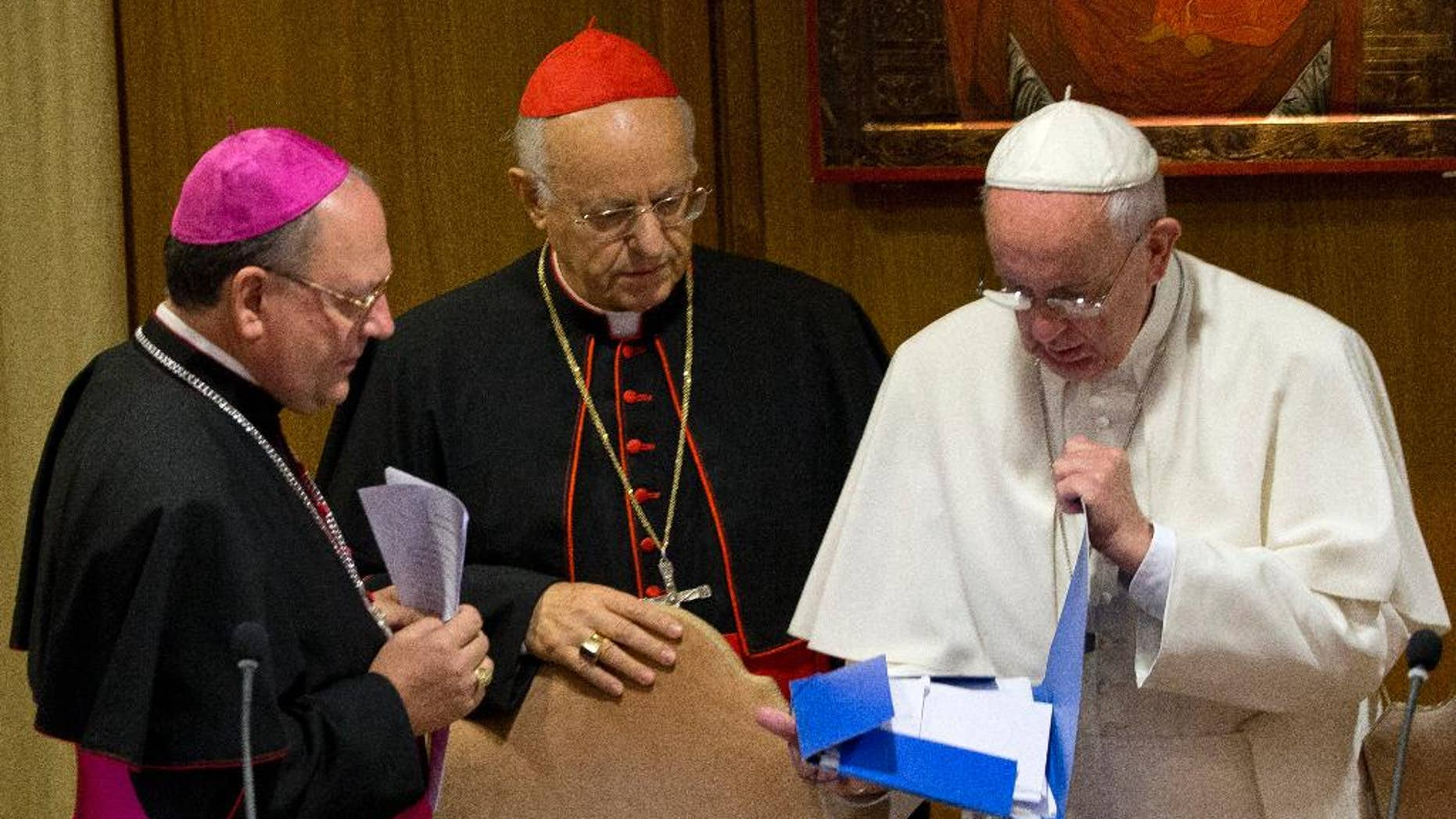 Pope Francis, right, checks a folder next to Bishop Fabio Fabene, left, and Cardinal Lorenzo Baldisseri as they arrive at a morning session of the two week-long Synod of bishops, at the Vatican, Tuesday, Oct. 6, 2015. (AP Photo/Alessandra Tarantino)