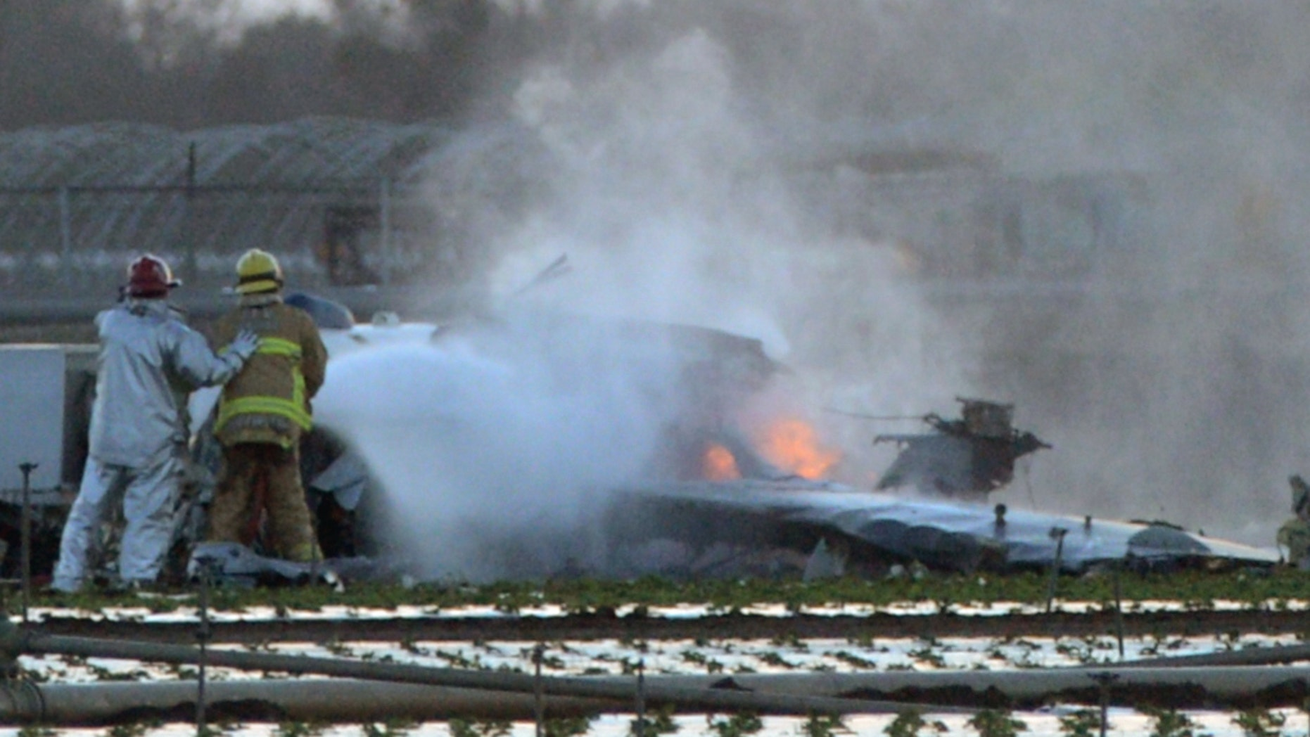 Oct. 29, 2014: Firefighters extinguish the remaining flames of a military airplane that crashed in a field near Naval Station Ventura County near Port Hueneme, Calif., killing the pilot