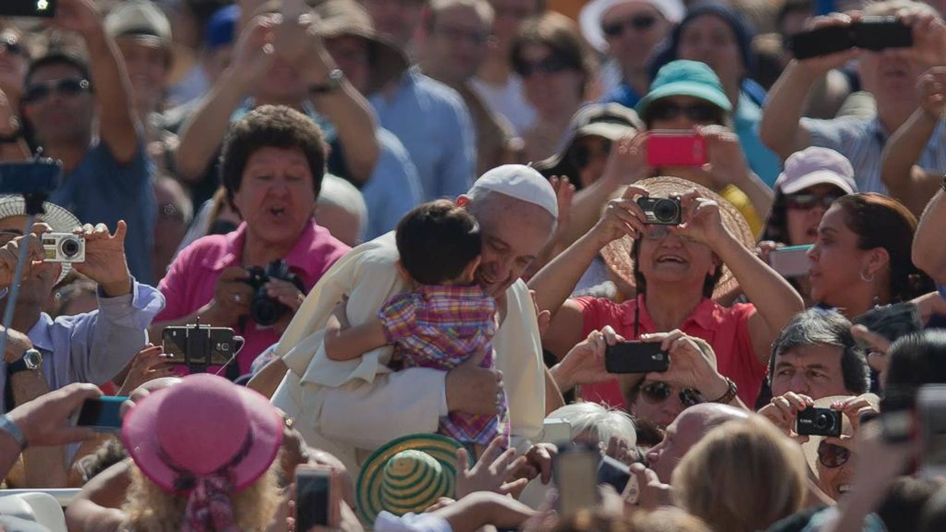 Pope Francis Pope Francis hugs a child as he arrives for his weekly general audience in St. Peter's Square at the Vatican, Wednesday, May 13, 2015. (AP Photo/Alessandra Tarantino)