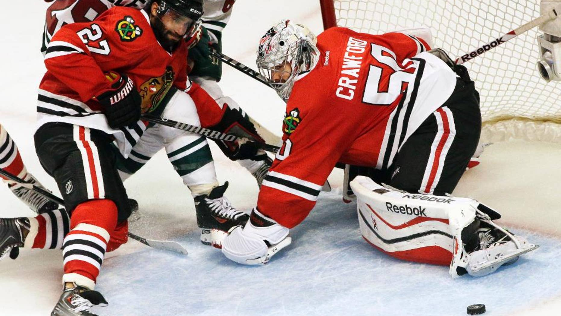 Chicago Blackhawks goalie Corey Crawford (50) blocks a shot as Johnny Oduya (27) battles for the puck against Minnesota Wild's Jason Pominville (29) and Mikael Granlund (64) during the third period in Game 5 of an NHL hockey second-round playoff series in Chicago, Sunday, May 11, 2014. The Blackhawks won 2-1. (AP Photo/Nam Y. Huh)