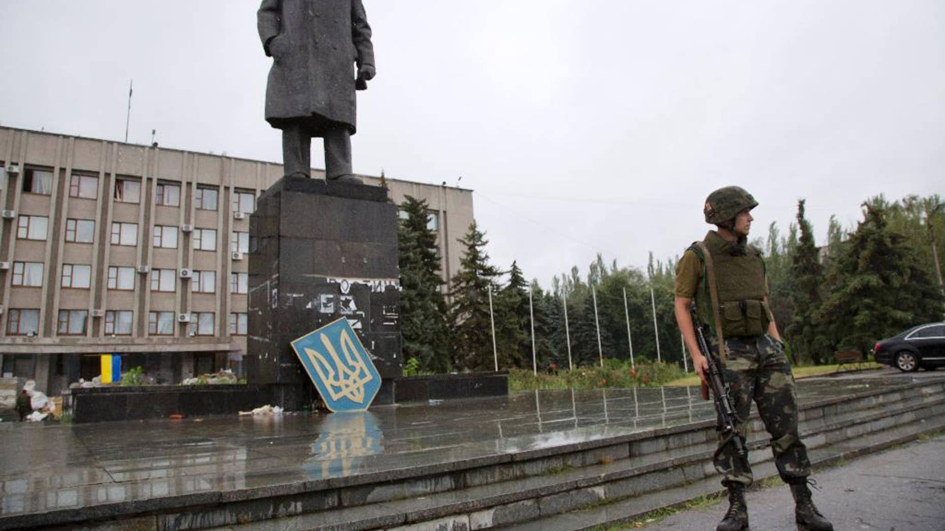 """A Ukrainian government army soldier guards the central square in the city of Slovyansk, Donetsk Region, eastern Ukraine Monday, July 7, 2014, with the Ukrainian State emblem leaning against a statue of Soviet Union founder Vladimir Lenin. Ukraine's president Petro Poroshenko has called the capture of the Pro-Russian separatist stronghold of Slovyansk a """"turning point"""" in the fight for control of the country's east. (AP Photo/Dmitry Lovetsky)"""