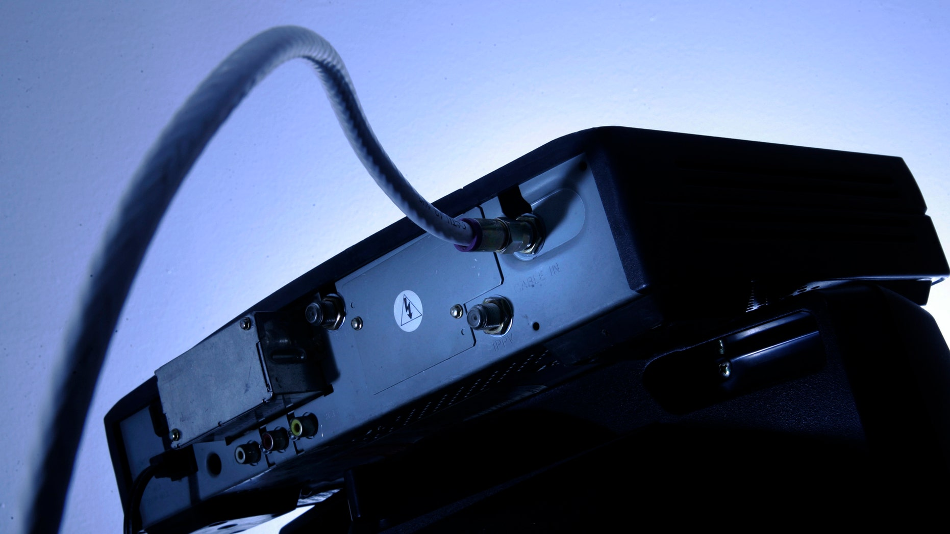 FILE - This Wednesday, May 30, 2007, file photo shows a cable box on top of a television in Philadelphia. Cable and satellite TV providers are ringing in 2018 with an unwelcomed gift: higher cable bills. Although annual rate hikes are inevitable, many consumers manage to lower their bills by pushing back and getting promotional rates. (AP Photo/Matt Rourke, File)