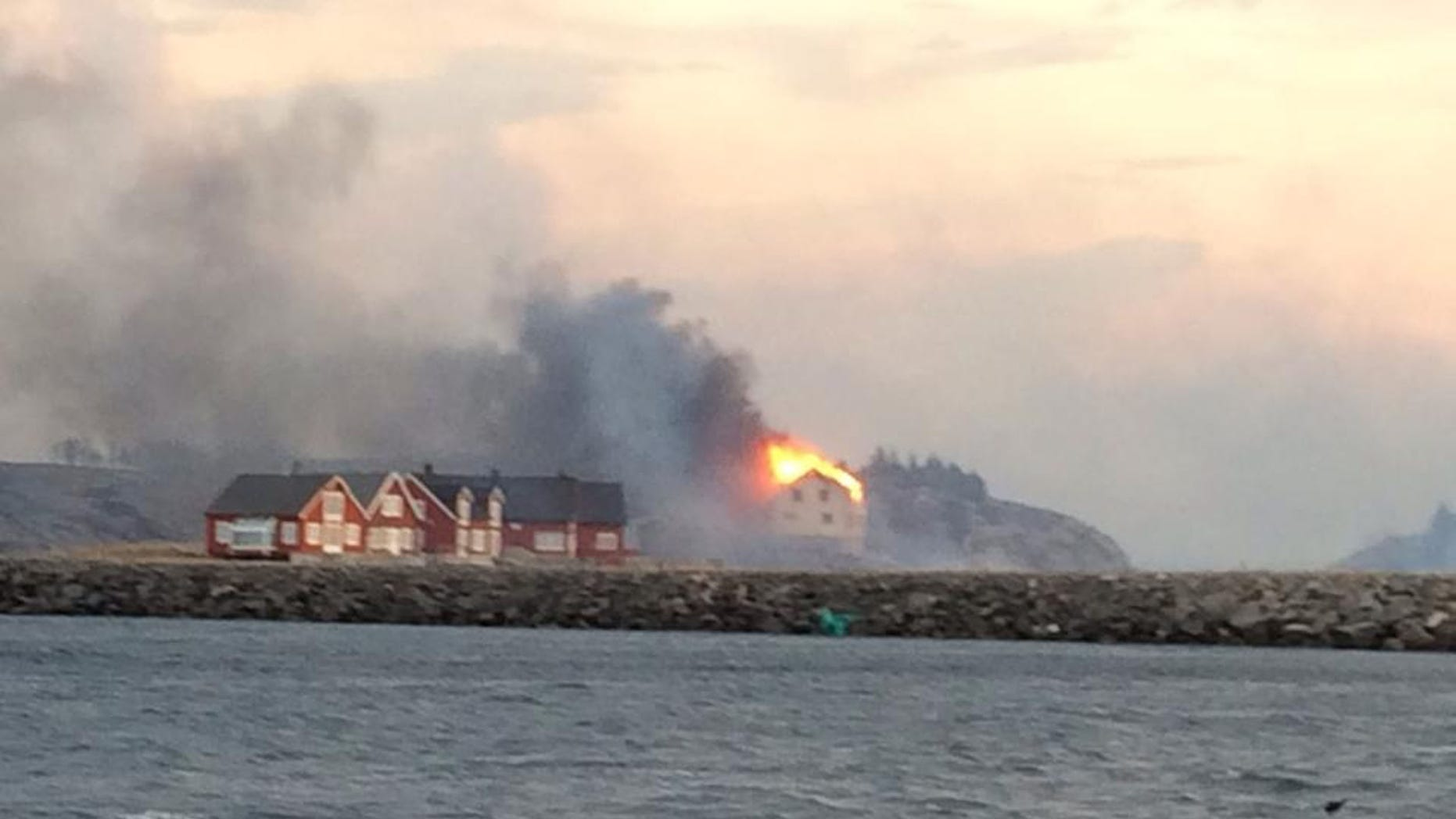 In this image taken from a rescue boat, buildings are seen on fire in Hasvaag, some 240 km north of Trondheim, Norway,  Tuesday, Jan. 28, 2014.  All of Hasvaag's 50-70 buildings have reportedly burned down. There have been no injuries, but all of the twenty people present have been evacuated. Many of the buildings are summer houses and cabins.  (AP Photo/NTB Scanpix, Redningsskoyta Harald V) NORWAY OUT