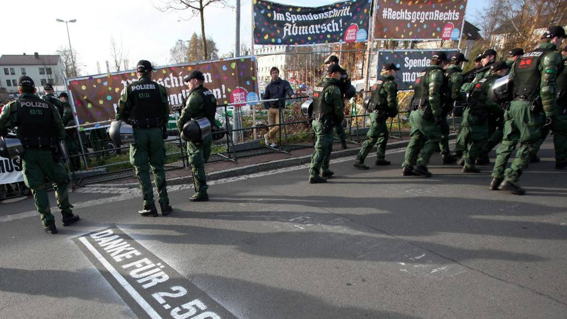 "In this picture taken Saturday, Nov. 15, 2014, police stand in front of banners reading ""Donate with every step, march"", top left, and ""#right against right"" top right, during a far-right march Wunsiedel, southern Germany. Letters on the ground say ""Thanks for euro 2,500!"". After failing to prevent neo-Nazis from staging an annual pilgrimage to the birthplace of Adolf Hitler's deputy Rudolf Hess, the Bavarian town decided to change tack this year. Residents and businesses pledged to pay 10 euro (US dollar 12.50) for every meter the neo-Nazis walked, and motivational signs were erected along the route of Saturday's march. Inge Schuster, a spokeswoman for the town, said Tuesday that the stunt received ""a great response,"" raising more than 10,000 euros for the group EXIT-Deutschland that helps people leave the neo-Nazi scene. (AP Photo/dpa, Fricke)"