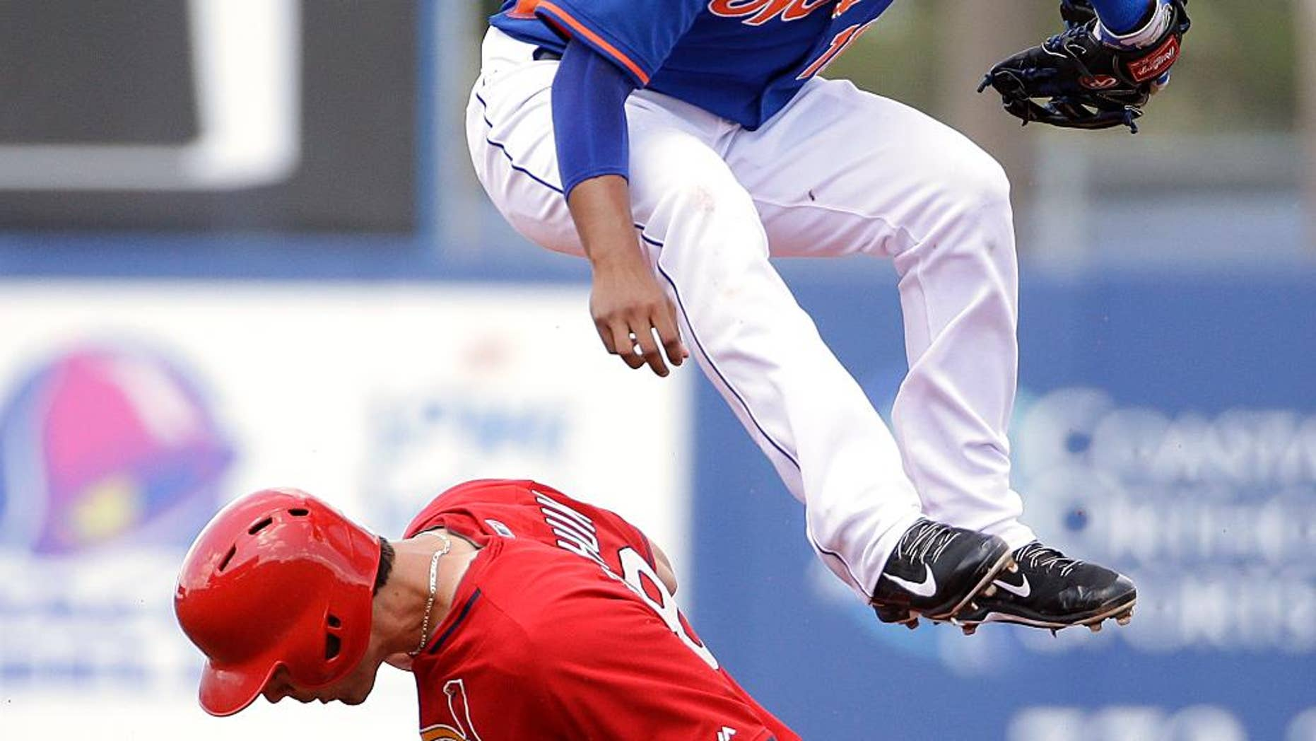 New York Mets shortstop Ruben Tejada, top, jumps over St. Louis Cardinals' Randal Grichuk after throwing to first base for a double play in the second inning of an exhibition spring training baseball game, Wednesday, March 12, 2014, in Port St. Lucie, Fla. (AP Photo/David Goldman)