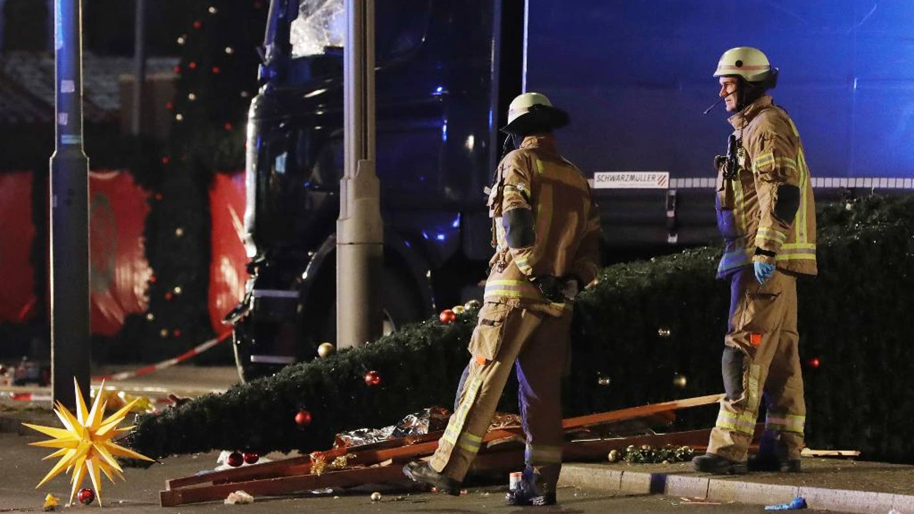 FILE - In this Monday, Dec. 19, 2016 file photo, firefighters stand next to a toppled Christmas tree after a truck ran into a crowded market and killed several people in Berlin, Germany. Though Tunisian Anis Amri had been under surveillance, he was able to hijack a truck and kill 12 people and wound dozens of others — the first mass-casualty Islamic extremist attack in Germany. (AP Photo/Michael Sohn)