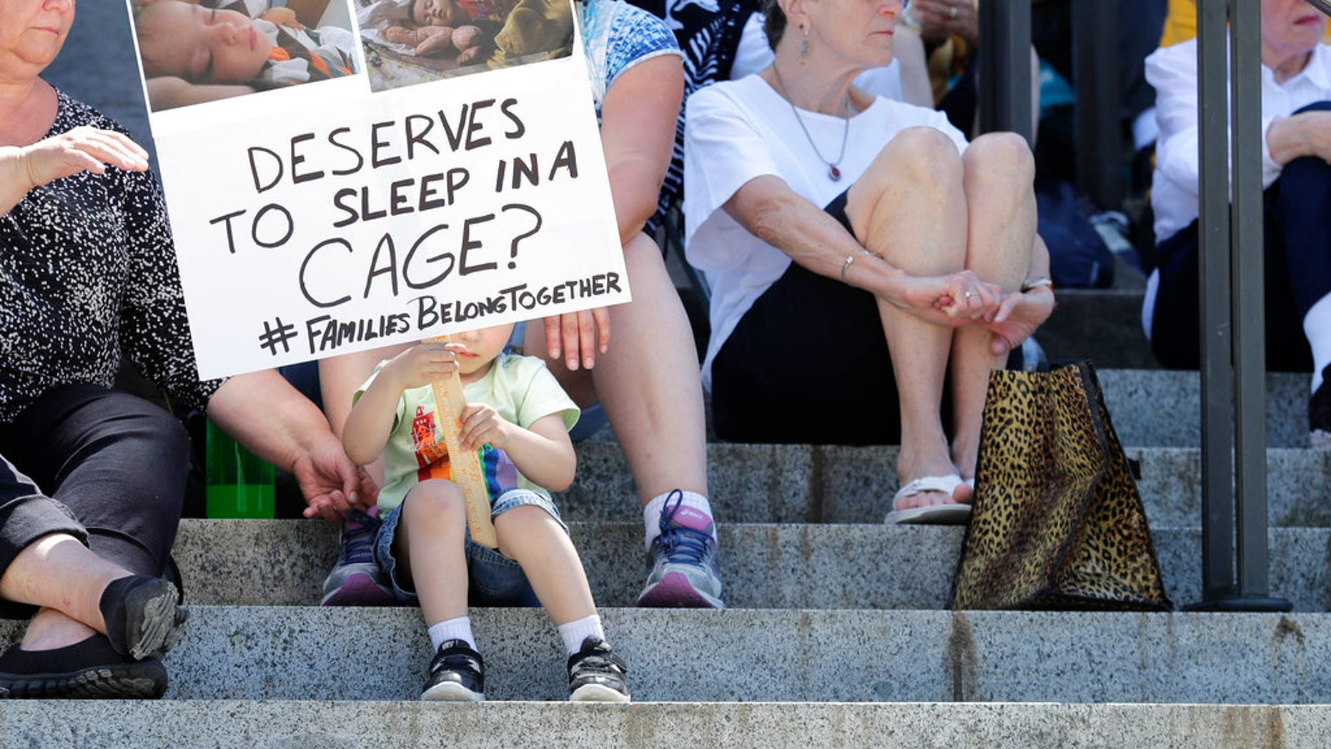 """Christopher Baker, 3, holds a sign that reads """"Which baby deserves to sleep in a cage?"""" as he attends a Poor People's Campaign rally with his mother, Katie Baker, behind sign, Monday, June 18, 2018, at the Capitol in Olympia, Wash. U.S. President Donald Trump defended his administration's border-protection policies Monday in the face of rising national outrage over the forced separation of migrant children from their parents. (AP Photo/Ted S. Warren)"""