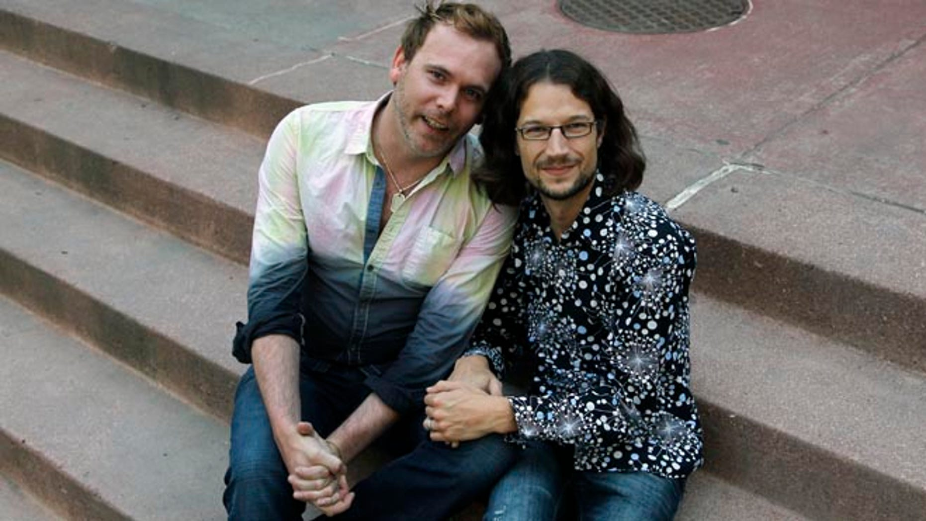 June 6, 2013: This file photo shows Dave Mullins, right, sitting for a portrait with his husband Charlie Craig, in Denver.
