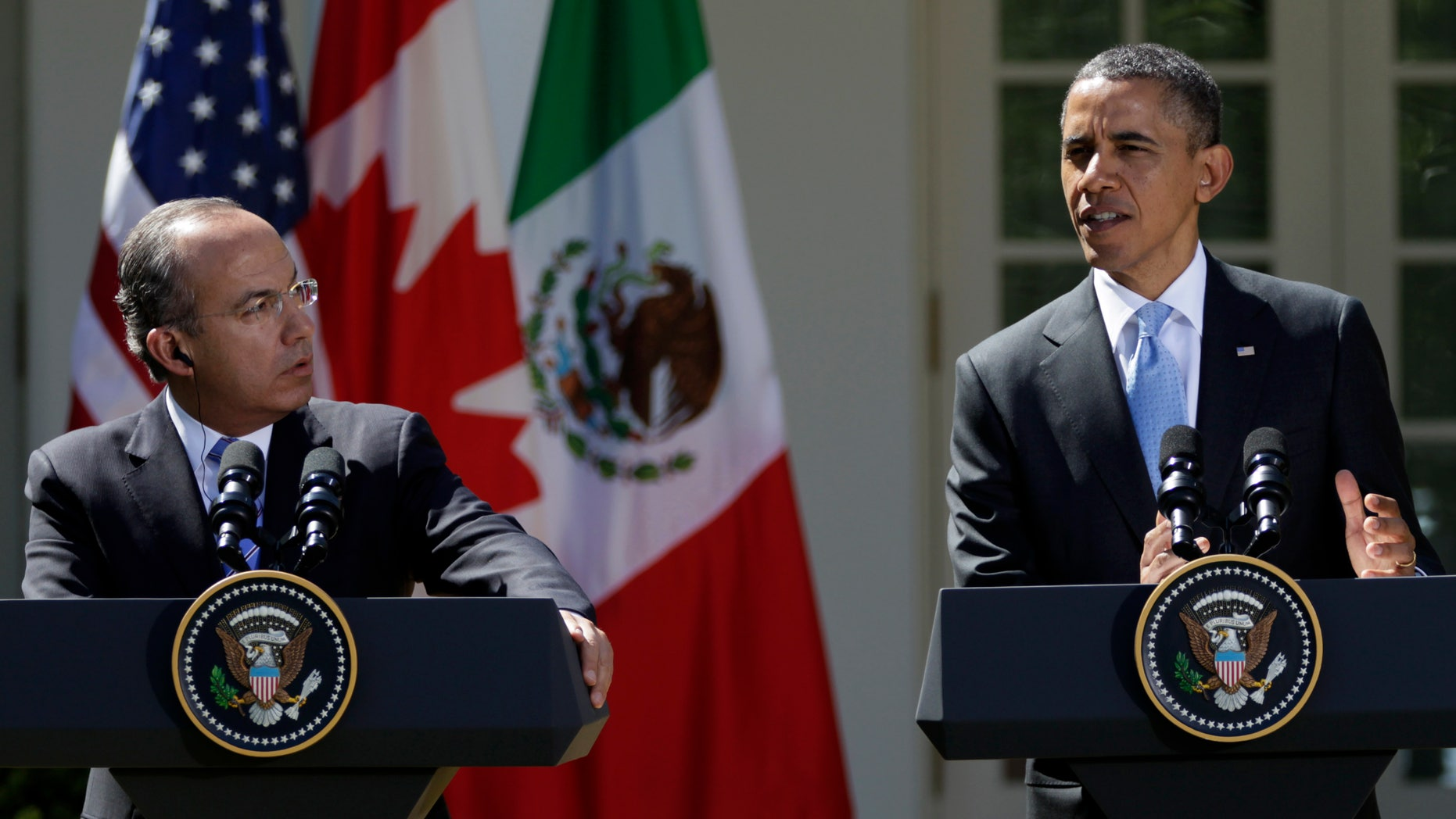 Mexican President Felipe Calderon watches at left as President Barack Obama speaks during a joint news conference with Canadian Prime Minister Stephen Harper, not seen, Monday, March 2, 2012, in the Rose Garden of the White House in Washington. (AP Photo/Carolyn Kaster)
