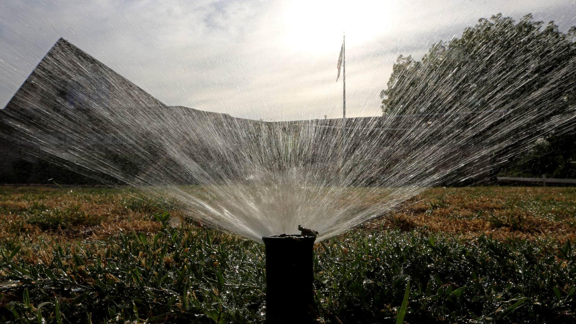 July 15, 2014: Sprinklers water a lawn in Sacramento, Calif.