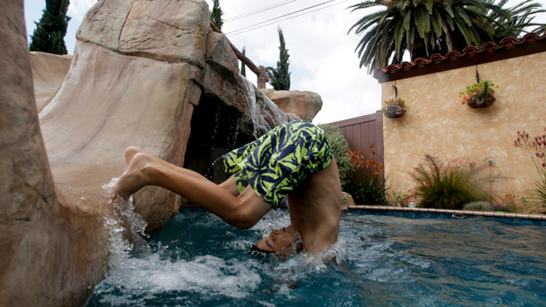 May 21, 2015: Jake Hall, 10, dives into a backyard pool in Long Beach, Calif. As residents struggle to reduce potable water consumption by 25 percent, the California Pool and Spa Association is promoting a campaign called Lets Pool Together and aggressively lobbying water districts to quash proposed bans on filling pools and spas.