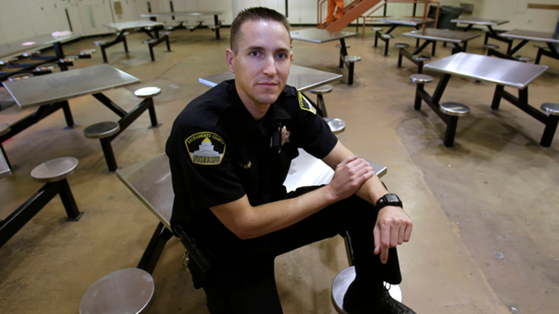 In this Wednesday, Aug. 14, 2013, photo, Sacramento County Deputy Sheriff Kenny Gouveia poses in the housing unit where he was attacked and injured while trying to settle a dispute between two inmates at the Sacramento County Jail.  Gouveia was off work for five days while he recovered from the injuries sustained when a 26-year-old inmate attacked him, slamming his head into a food cart and choking him.  County jails across California have seen a marked increase in violence since they began housing thousands of offenders who previously would have gone to state prisons.
