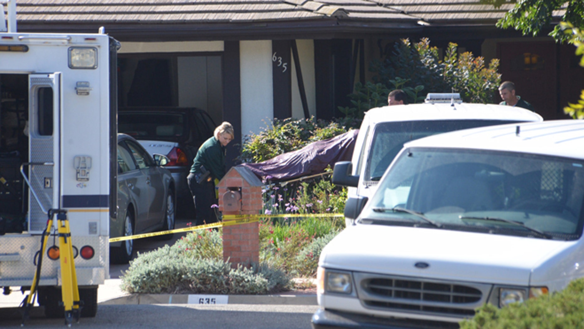 Aug. 12, 2014: Investigators remove a body from a home in Goleta, Calif., where four people and a dog were found stabbed to death the night before.