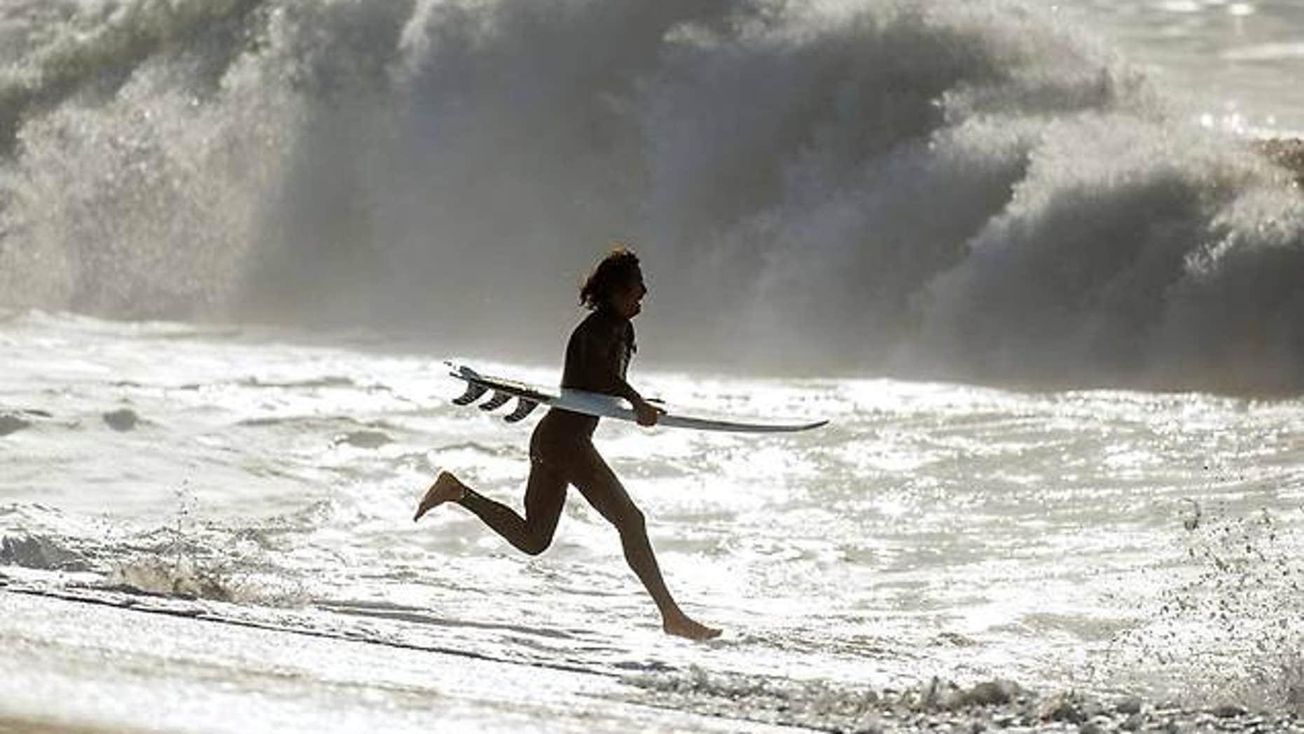 A surfer runs into the ocean at Seal Beach, Calif. on Thursday.