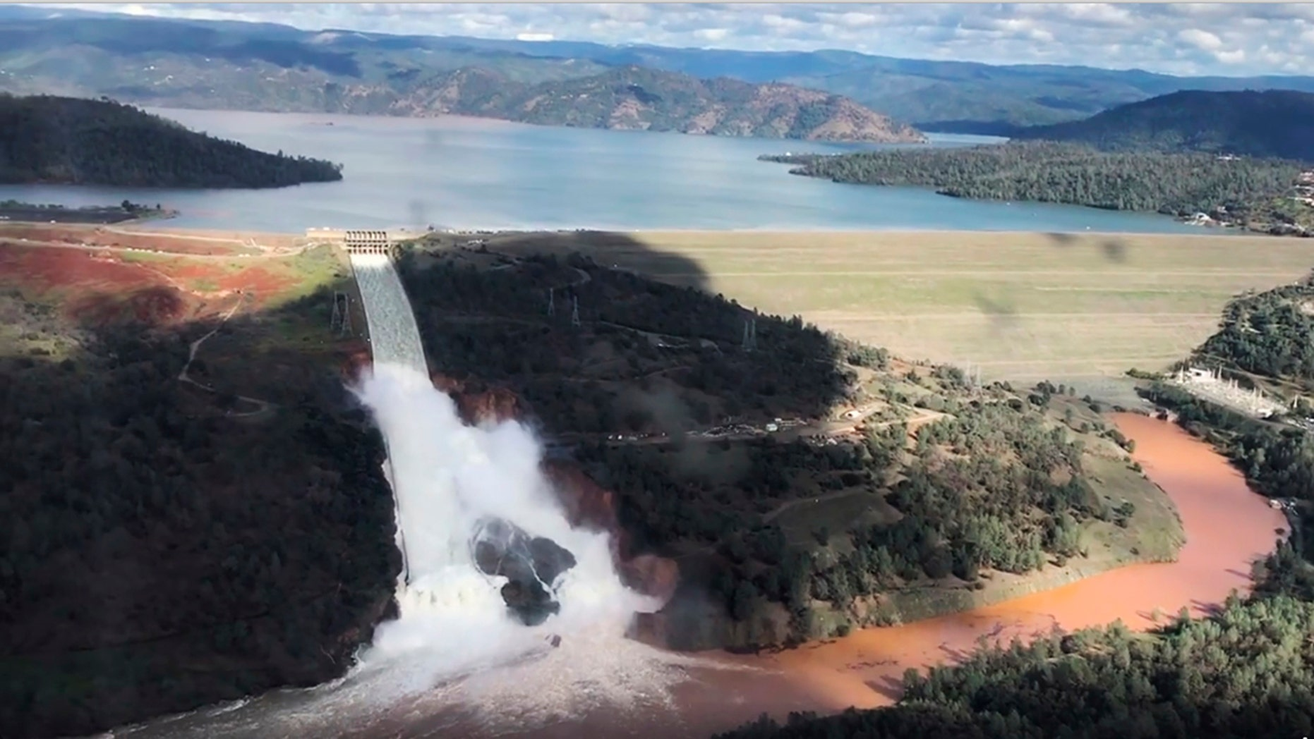 Feb. 10, 2017: This image from video provided by the office of Assemblyman Brian Dahle shows water flowing over an emergency spillway of the Oroville Dam in Oroville, Calif., during a helicopter tour by the Butte County Sheriff's office.
