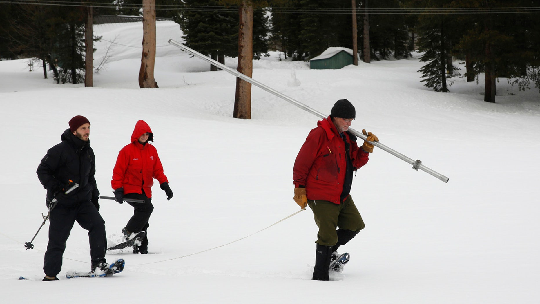 Feb. 2, 2017: Frank Gehrke, right, chief of the California Cooperative Snow Surveys Program for the Department of Water Resources, carries the snowpack measuring tube as he crosses a snow covered meadow while conducting the second manual snow survey of the season in Echo Summit, Calif.