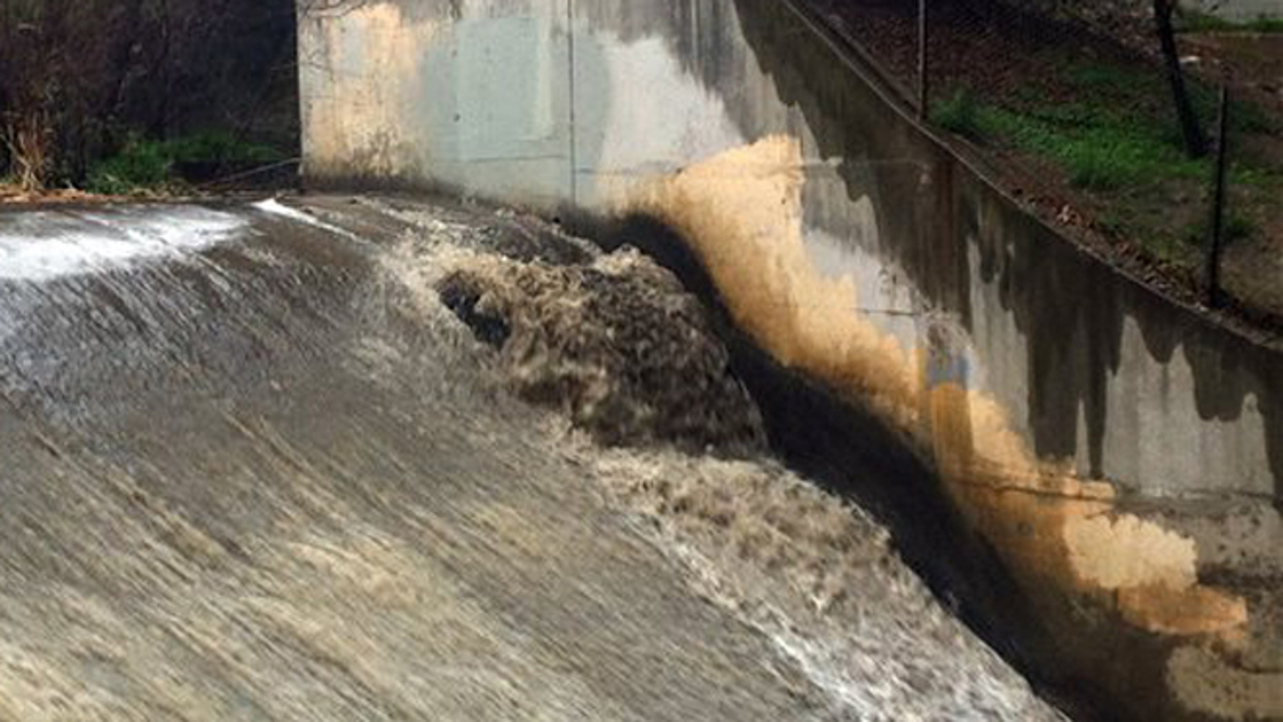 Runoff gushes down a spillway in the Arroyo Seco, which translates to 'dry creek' or 'dry stream' in Spanish, in Pasadena, Calif., as rain drenches the region Sunday, Jan. 31, 2016.
