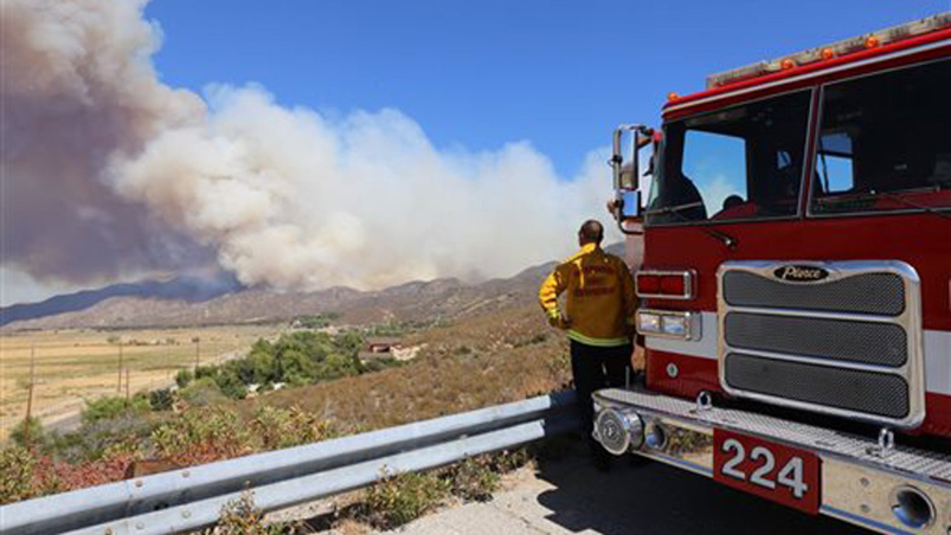 A San Bernardino County Fire Department engine and its crew keep watch over Summit Valley, Calif., as a wildfire burns east of Silverwood Lake on Sunday, Aug. 7, 2016.