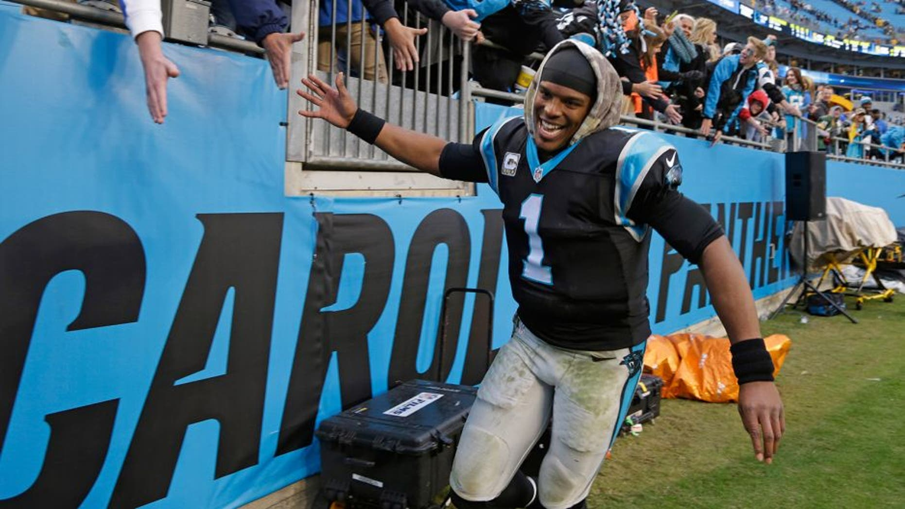 Carolina Panthers' Cam Newton (1) celebrates with fans after an NFL football game against the Green Bay Packers in Charlotte, N.C., Sunday, Nov. 8, 2015. The Panthers won 37-29. (AP Photo/Bob Leverone)