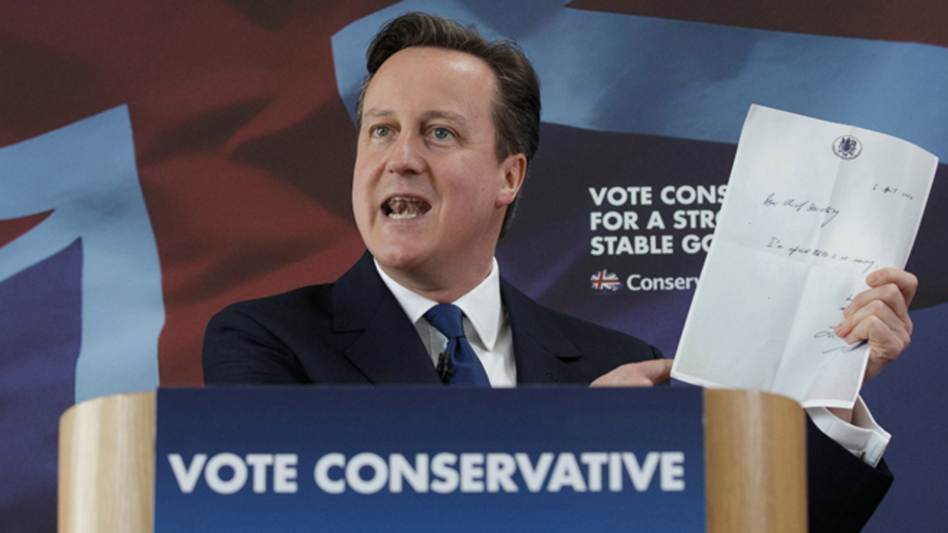 """British Prime Minister David Cameron holds up a photocopied note left by former chief secretary to the Treasury Liam Byrne on his desk after Labour's 2010 election defeat, which reads """"Dear Chief Secretary, I'm afraid there is no money. Kind regards - and good luck! Liam."""" as he delivers a speech at the Ambleside Sports Club in Nuneaton, England, Sunday, May 3, 2014. Britain goes to the polls in a General Election on May 7. (AP Photo/Tim Ireland, Pool)"""