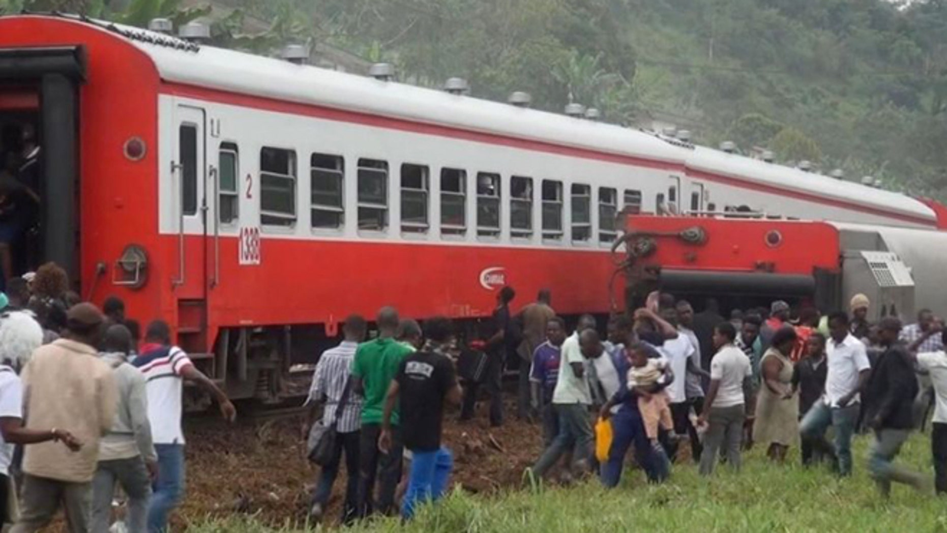 People walk beside a derailed train carriage after an accident in Eseka, Cameroon, Friday, Oct. 21, 2016.  (Equinox TV via AP)