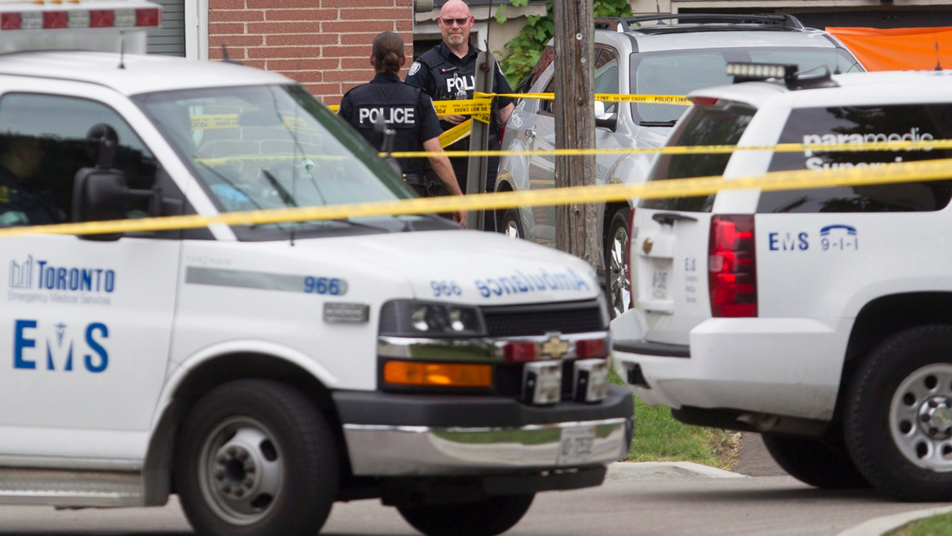 Aug. 25, 2016: Police stand in front of a house in Scarborough, Ont. after three people were killed in a crossbow incident