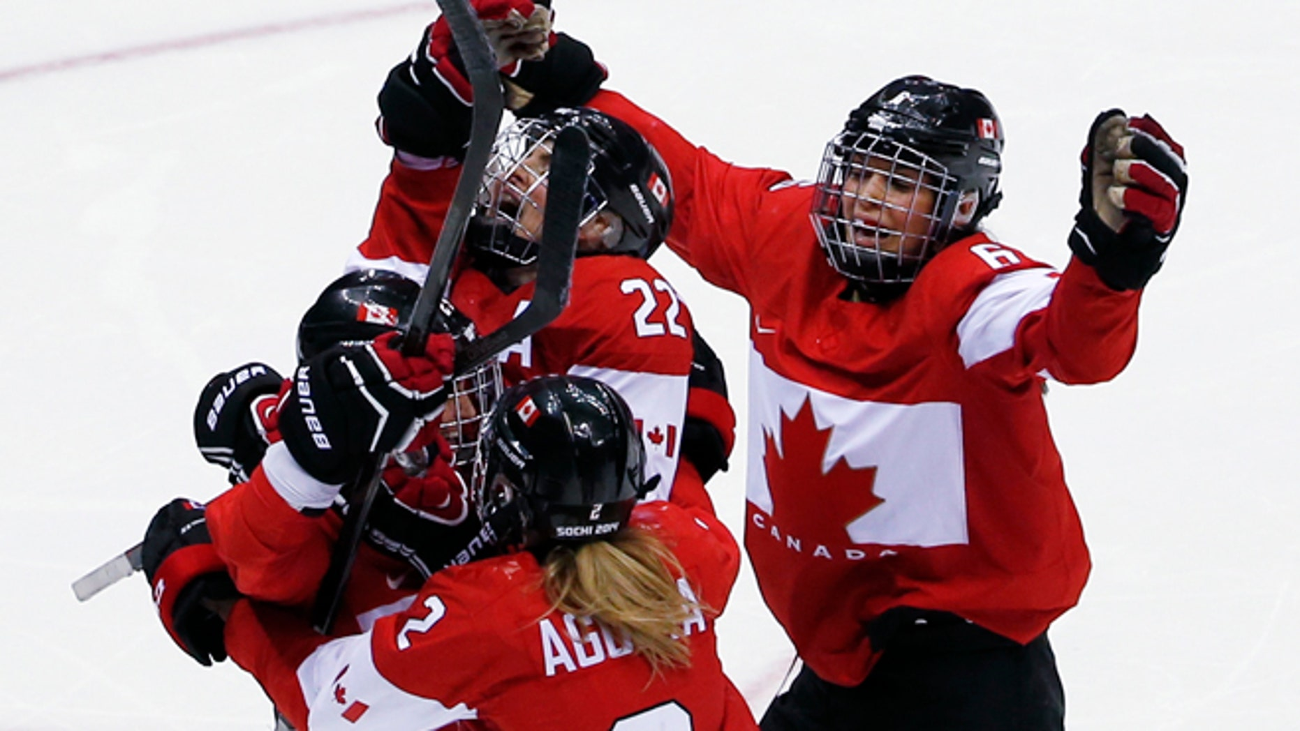 Feb. 20, 2014: Marie-Philip Poulin of Canada (29) is swarmed by teammates after scoring the game-winning goal in overtime against USA at the women's gold medal ice hockey game at the 2014 Winter Olympics in Sochi, Russia.