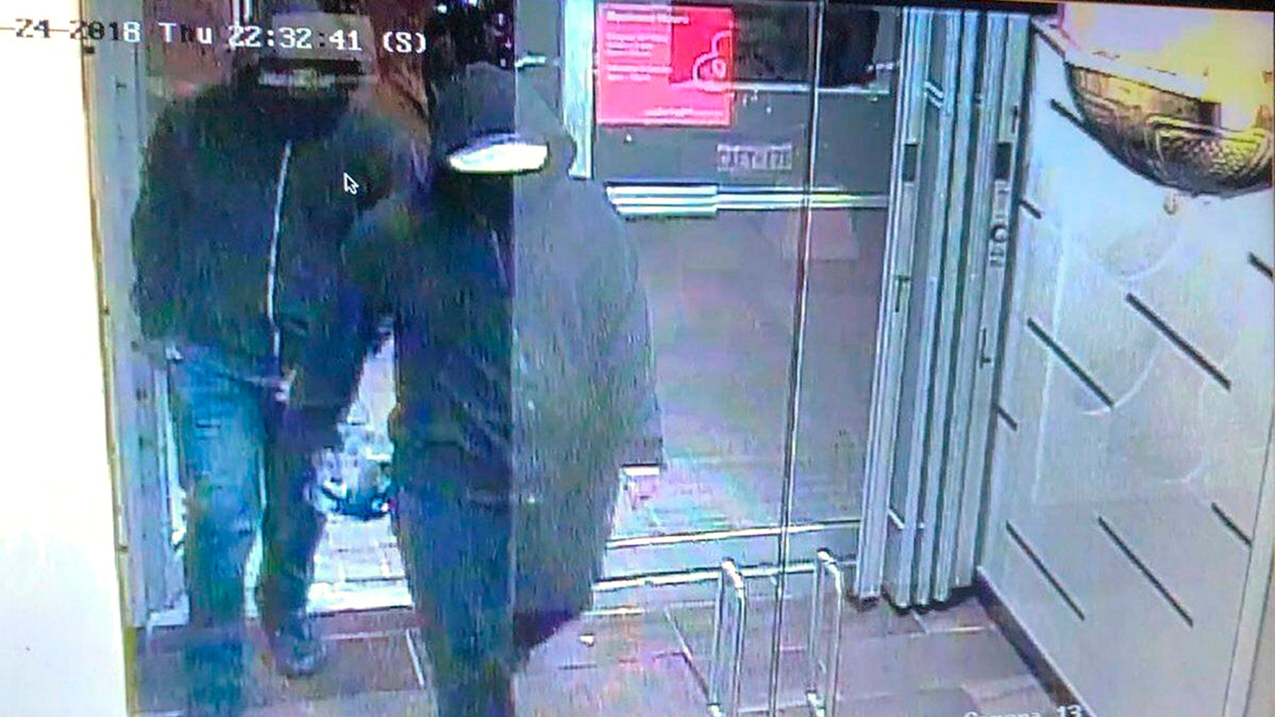 """In this image made from CCTV footage released by Peel Regional Police, two suspects enter a glass doorway of the Bombay Bhel Indian restaurant, late Thursday, May 24, 2018, in Mississauga, suburb of Toronto, Canada. Police are searching for the two suspects in connection with the explosion caused by """"improvised explosive device"""" that ripped through the restaurant, wounding 15 people, Canadian police said."""