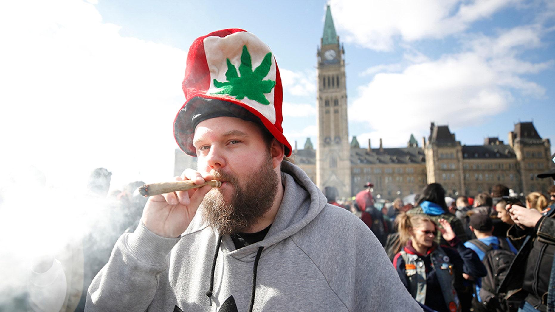 A man smokes marijuana during the annual 4/20 marijuana rally on Parliament Hill in Ottawa, Ontario, Canada, April 20, 2018