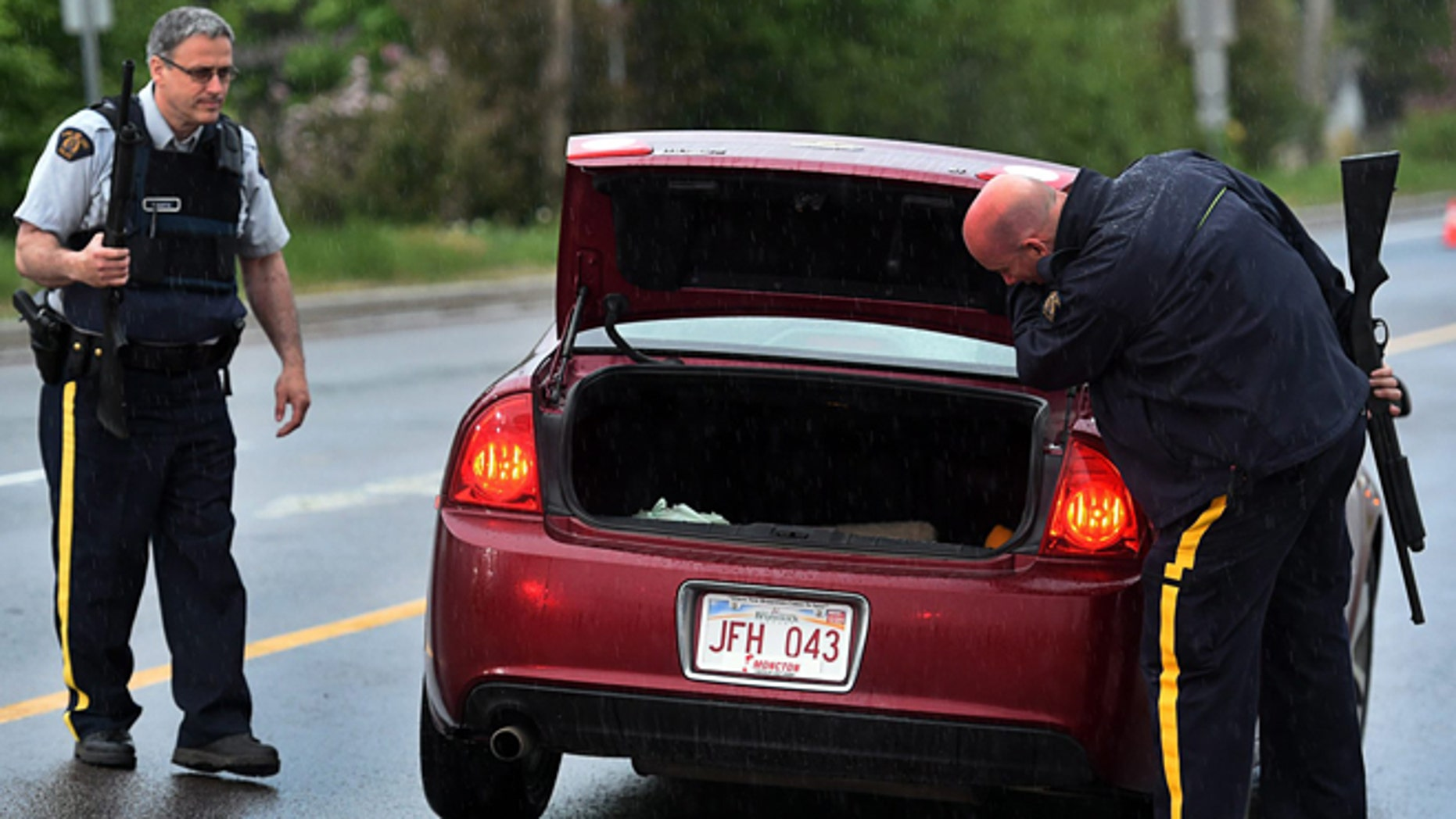 June 5, 2014: Police officers check a car at a roadblock in Moncton, New Brunswick.