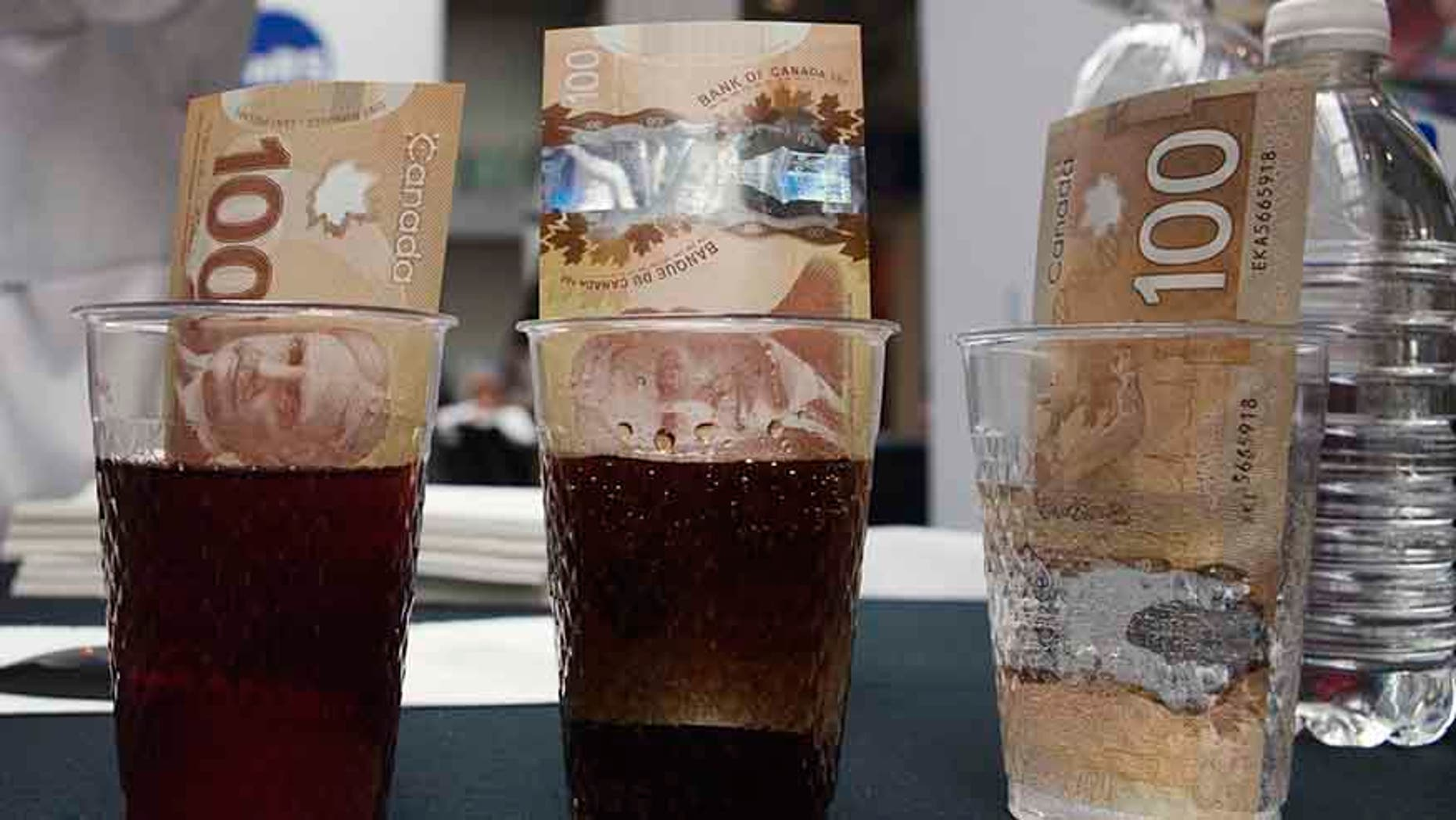 Canadian 100 dollar bills made of polymer are placed in glasses of juice, cola and water.