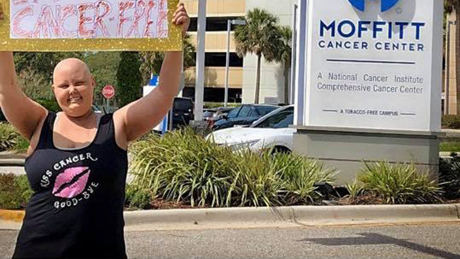 Cori holds sign outside Moffitt Cancer Center
