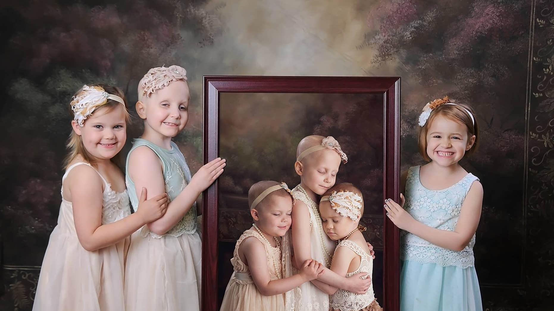 Rheanna, Ainsley and Rylie pose with the original photo of them taken two years ago.