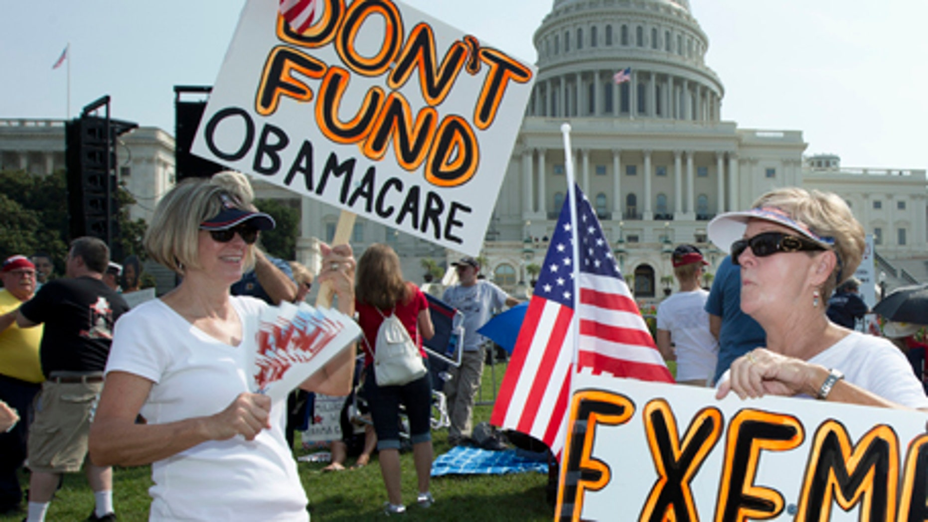 "FILE -- Sept. 10, 2013: Linda Norman, right, and Joanna Galt, both from Florida, hold their banners during a ""Exempt America from Obamacare"" rally on the West Lawn of the Capitol in Washington."