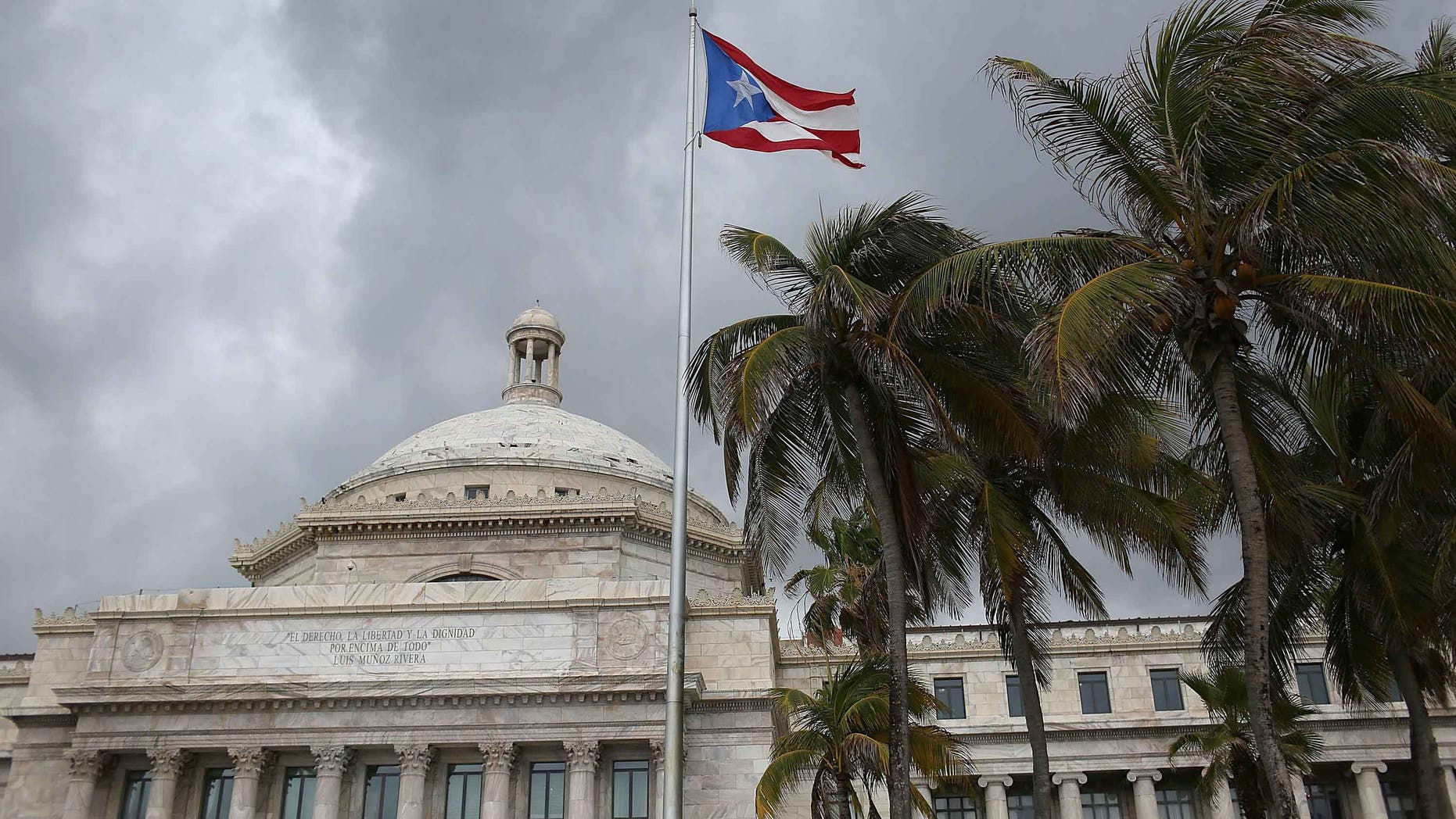 SAN JUAN, PUERTO RICO - JUNE 30:  The Puerto Rican flag flies above the Capitol a day after Puerto Rican Governor Alejandro Garcia Padilla gave a televised speech regarding the governments $72 billion debt on June 30, 2015 in San Juan, Puerto Rico.  The Governor said in his speech that the people will have to sacrifice and share in the responsibilities for pulling the island out of debt.  (Photo by Joe Raedle/Getty Images)