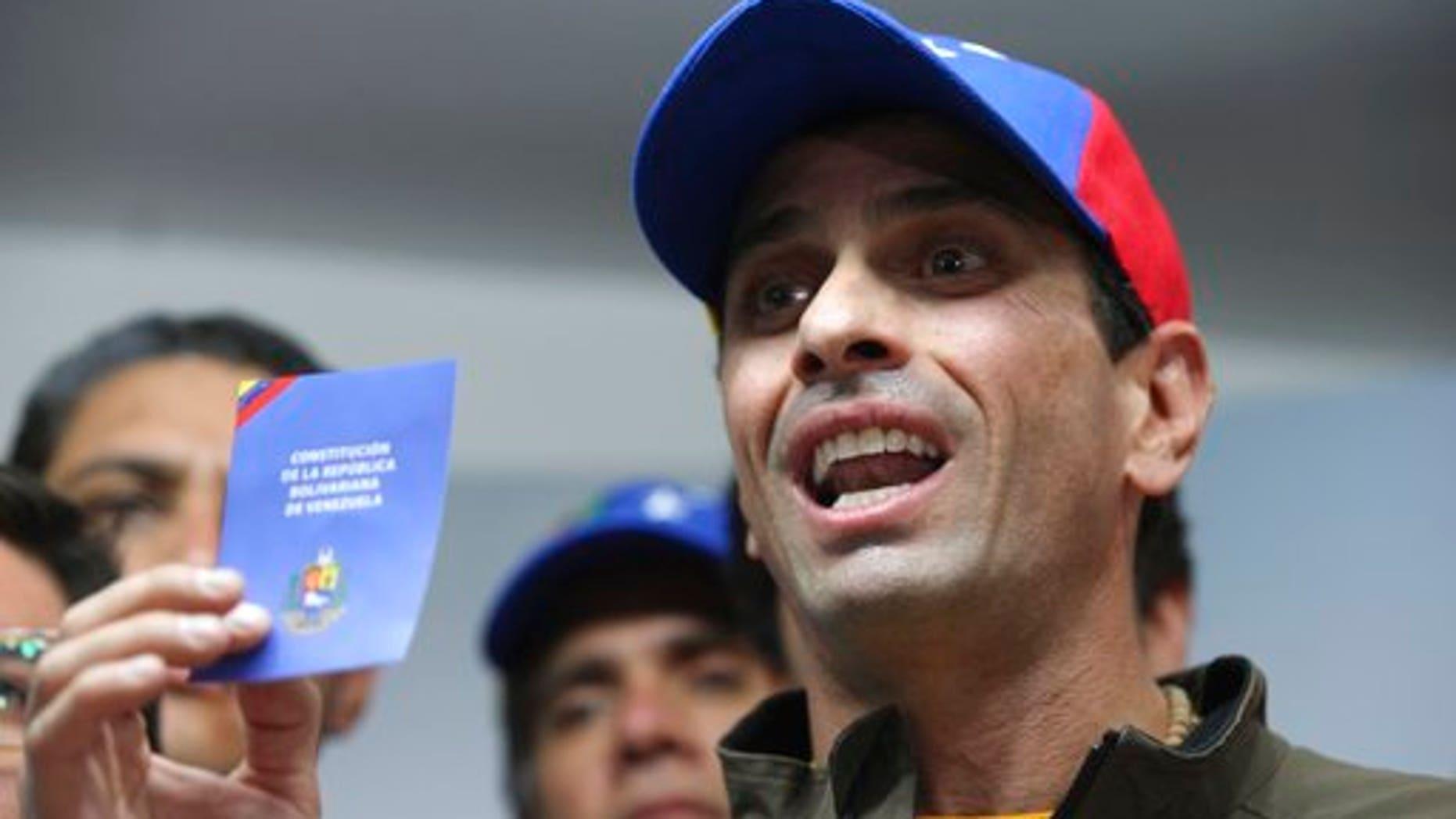 Opposition leader Henrique Capriles displays a copy of Venezuela's Constitution during a news conference in Caracas, Venezuela, Thursday, April 6, 2017.