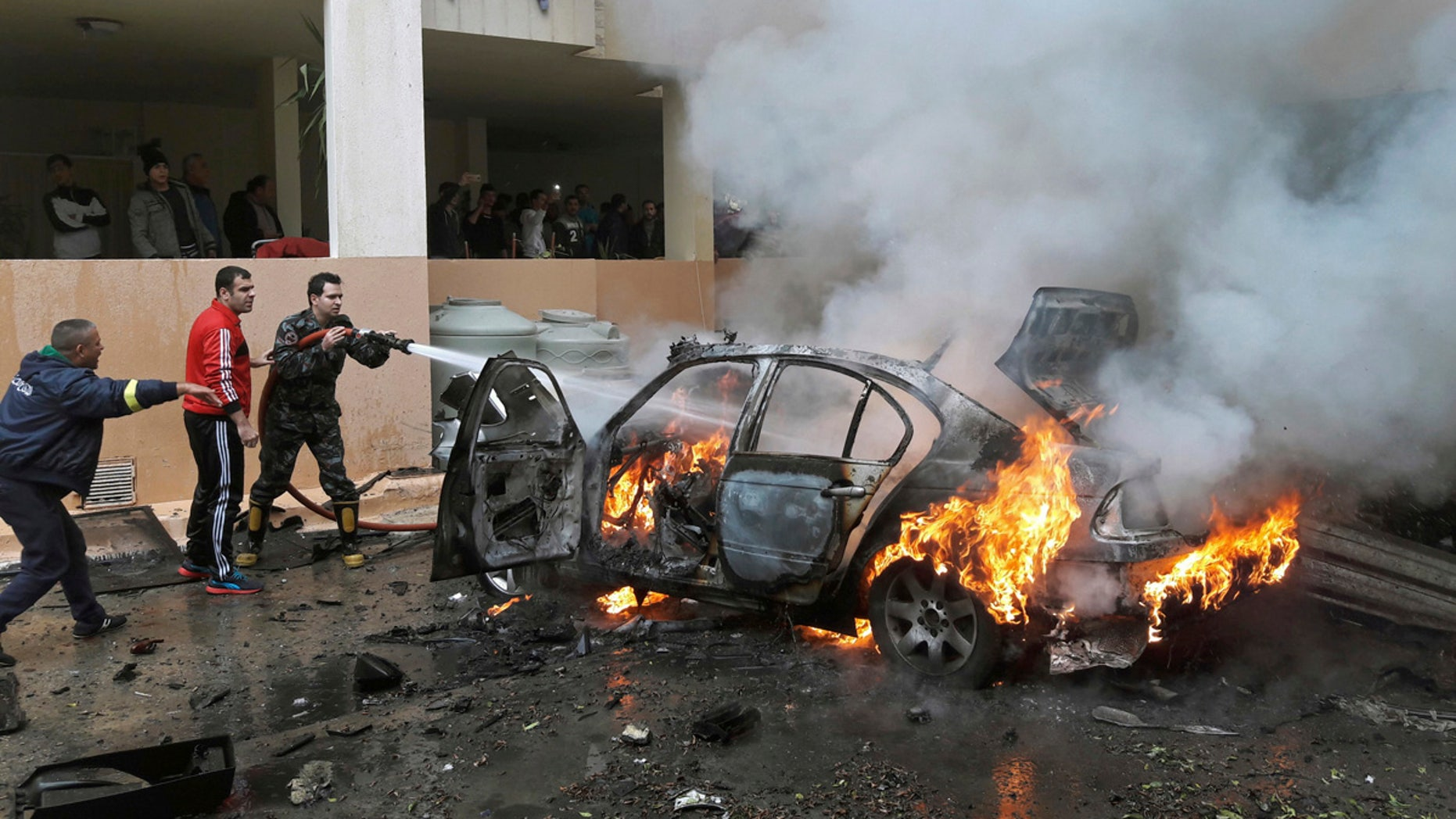 Firefighters extinguish a burning car that was destroyed in a bombing in the southern port city of Sidon, Lebanon, Sunday, Jan. 14, 2018