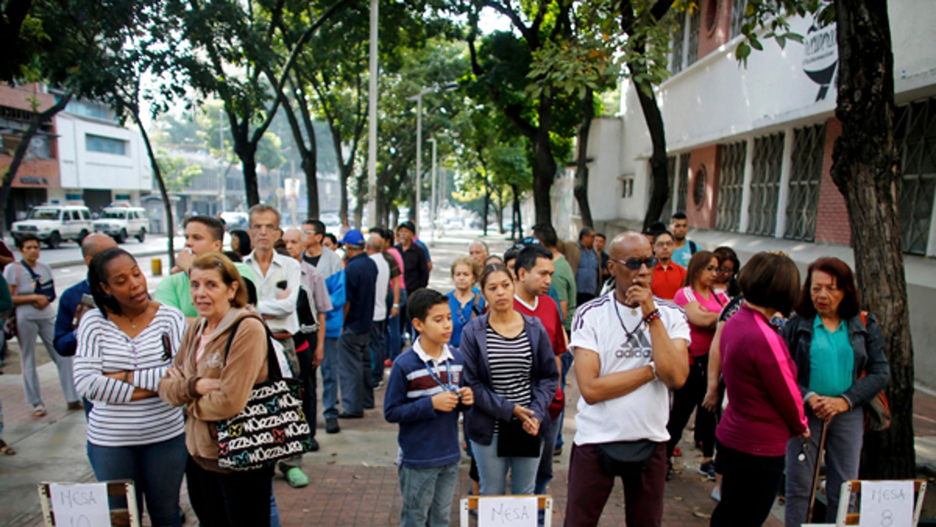 Voters wait outside of a poll station to enter to cast their ballot during the election for a constitutional assembly in Caracas, Venezuela, Sunday, July 30, 2017. President Nicolas Maduro asked for global acceptance on Sunday as he cast an unusual pre-dawn vote for an all-powerful constitutional assembly that his opponents fear he'll use to replace Venezuelan democracy with a single-party authoritarian system.