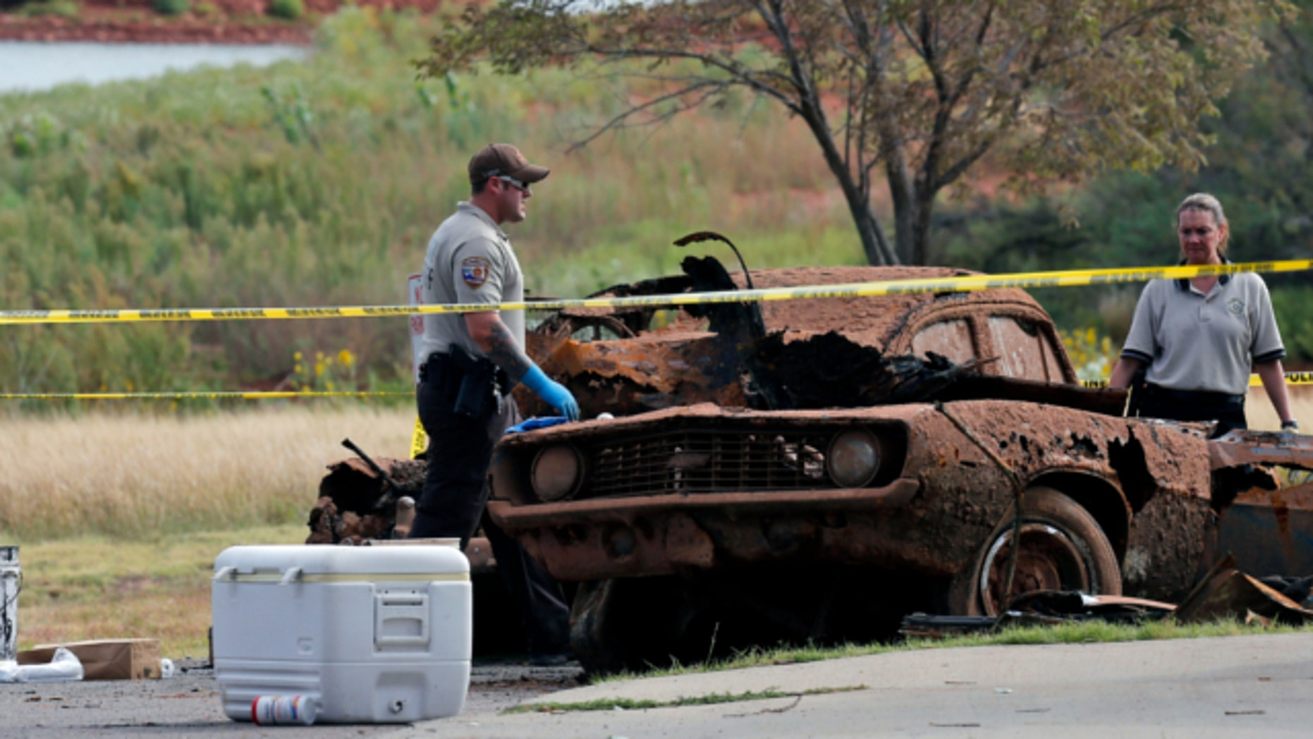 Sept. 18, 2013. Law enforcement officials from multiple agencies examine the two cars pulled from Foss Lake, in Foss, Okla.
