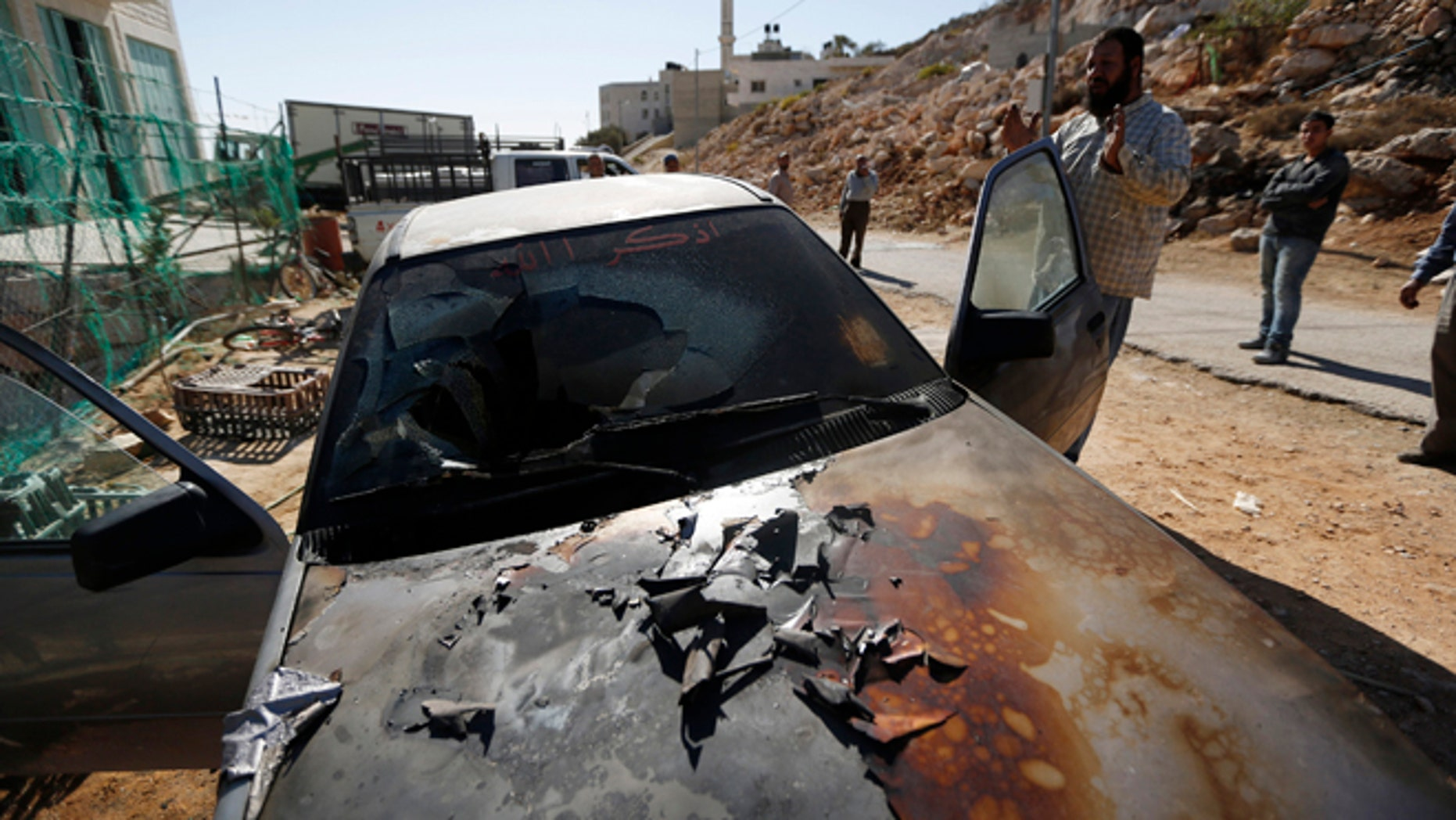 """Oct. 10: A Palestinian man gestures near a damaged car in the West Bank village of Burka, near Ramallah. An Israeli police spokesperson said on Thursday three cars were damaged overnight and the words """"Geulat Tzion loves Tomer Hazan"""" were scrawled in Hebrew on a wall of the mosque. Geulat Tzion is an illegal Jewish settler-outpost in the West Bank where structures were demolished by Israeli forces a day earlier and Tomer Hazan is an Israeli soldier who was killed by a Palestinian on September 21."""