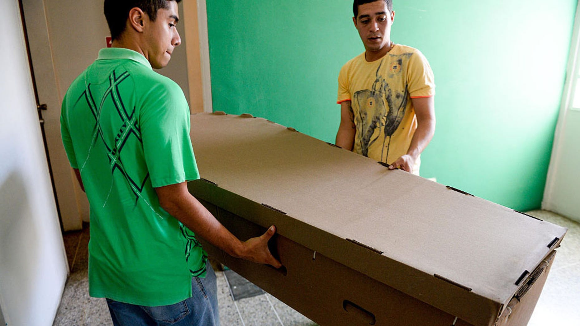 Two young men carry a cardboard coffin in Barquisimeto, Venezuela on August 9, 2016.Due to the high cost and the shortage of materials that make the acquisition of coffins difficult in Venezuela, they are being made in cheap timber planks and even cardboard. (Photo credit FEDERICO PARRA/AFP/Getty Images)