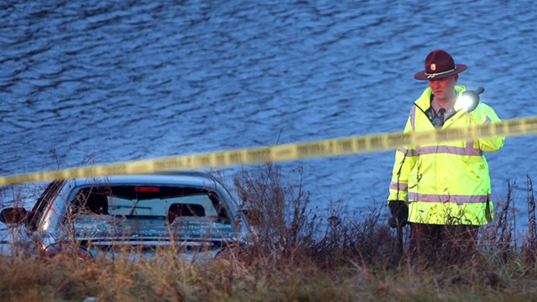Nov. 21, 2013: A police officer investigates the scene where six people were rescued after their car went into a holding pond near a highway exit ramp.
