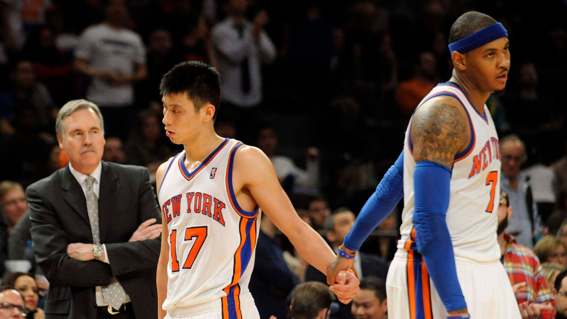 New York Knicks' Carmelo Anthony, right, holds Jeremy Lin's hand as he leaves the game after fouling out during the fourth quarter of an NBA basketball game against the New Jersey Nets, Monday, Feb. 20, 2012, at Madison Square Garden in New York. The Nets defeated the Knicks 100-92. Anthony shot 4 of 11 and scored 11 points. Lin finished with 21 points, nine assists and seven rebounds. At left is Knicks coach Mike D'Antoni. (AP Photo/Bill Kostroun)