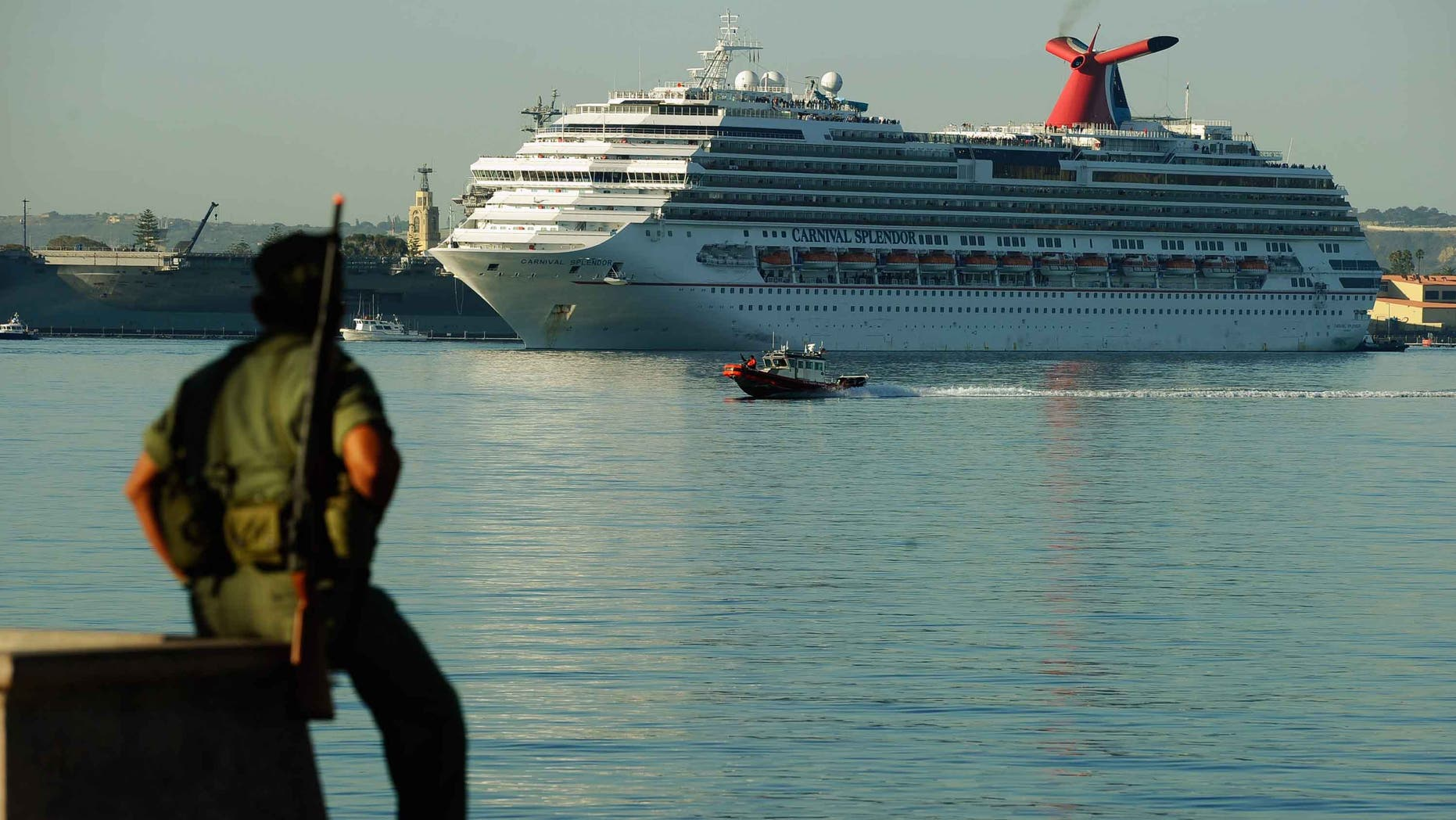 SAN DIEGO - NOVEMBER 11:  The stranded Carnival Splendor cruise ship is towed to San Diego Harbor by tug boats on November 11, 2010 in San Diego, California.  The cruise ship lost power and became stranded off of California's coast early Monday after a fire in the engine room.  A military service member in observance of Veterans Day looks on. (Photo by Kevork Djansezian/Getty Images)