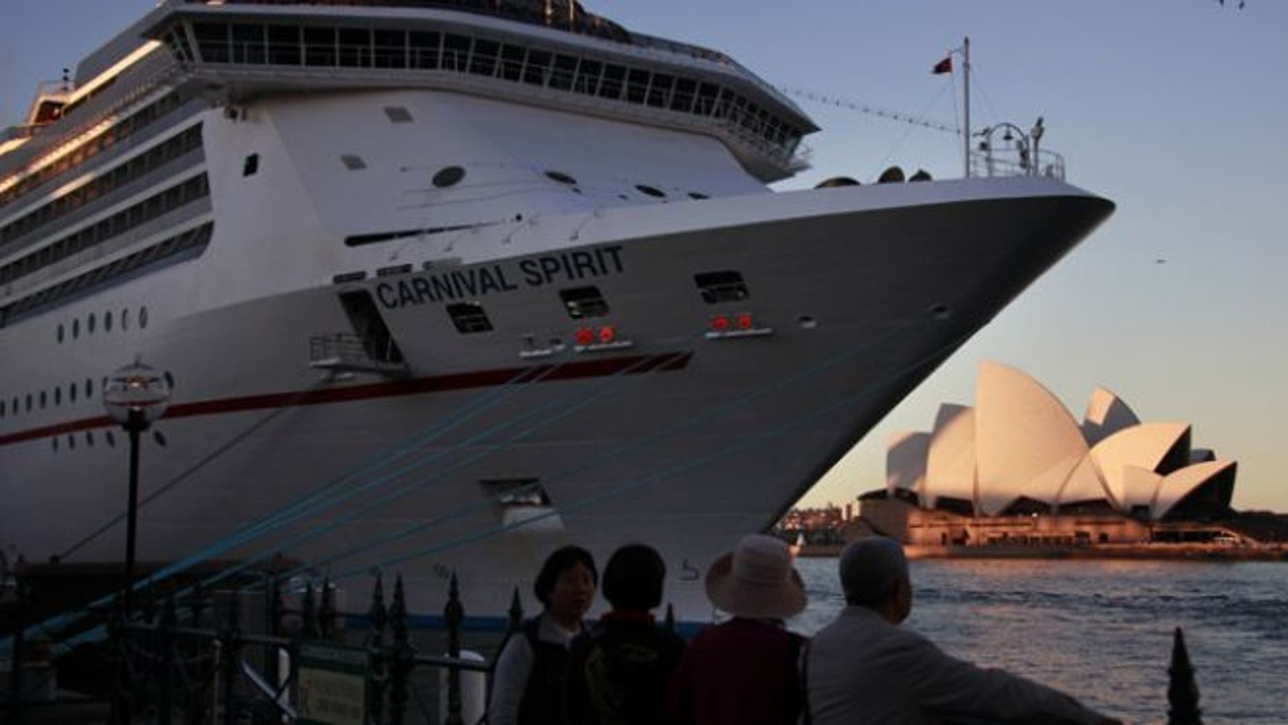 """May 9, 2013: Onlookers stand below a Carnival Cruise Lines ship called the """"Carnival Spirit"""" as it sits docked opposite the Sydney Opera House."""