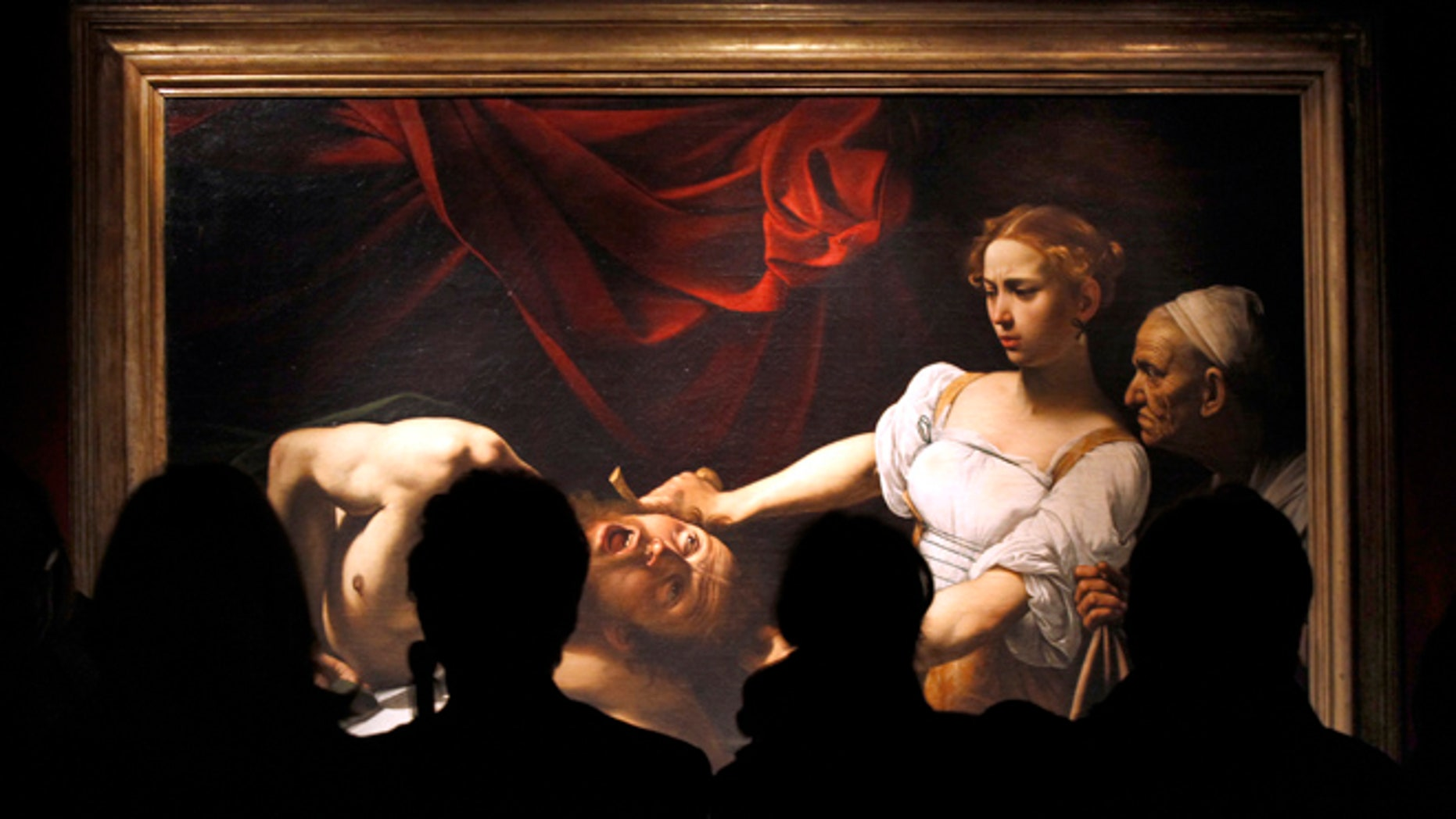 """FILE 2010: Visitors stand near Caravaggio's """"Judith Beheading Holofernes"""" painting during an exhibition to celebrate the Baroque master on the 400th anniversary of his death at the Scuderie del Quirinale building in Rome."""