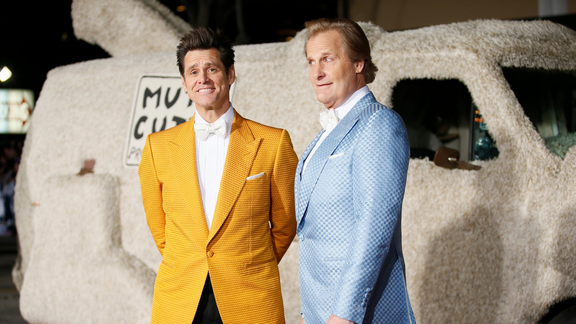"""Actors Jim Carrey (L) and Jeff Daniels arrive in a van decorated as a dog at the world premiere of the film """"Dumb and Dumber To"""" in Los Angeles, November 3, 2014.   REUTERS/Danny Moloshok   (UNITED STATES - Tags: ENTERTAINMENT) - RTR4CPGL"""